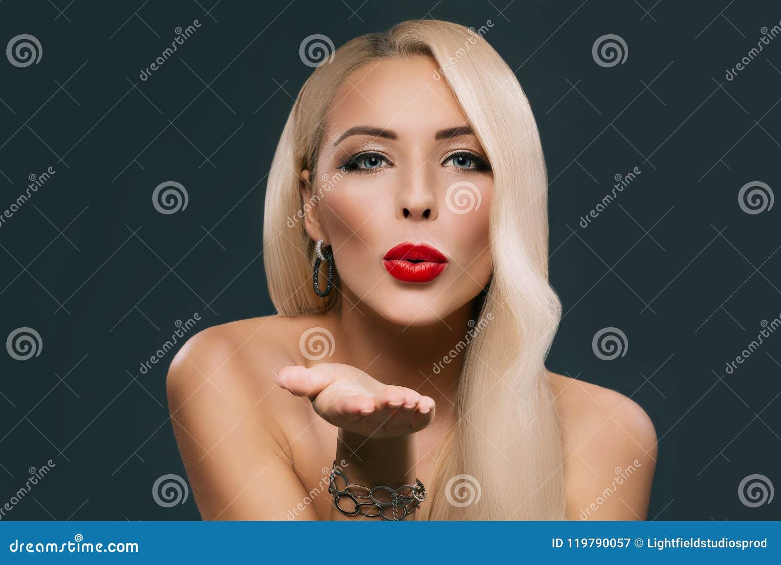 Piękna blondynki kobieta z makeup i fryzury dmuchaniem całuje,