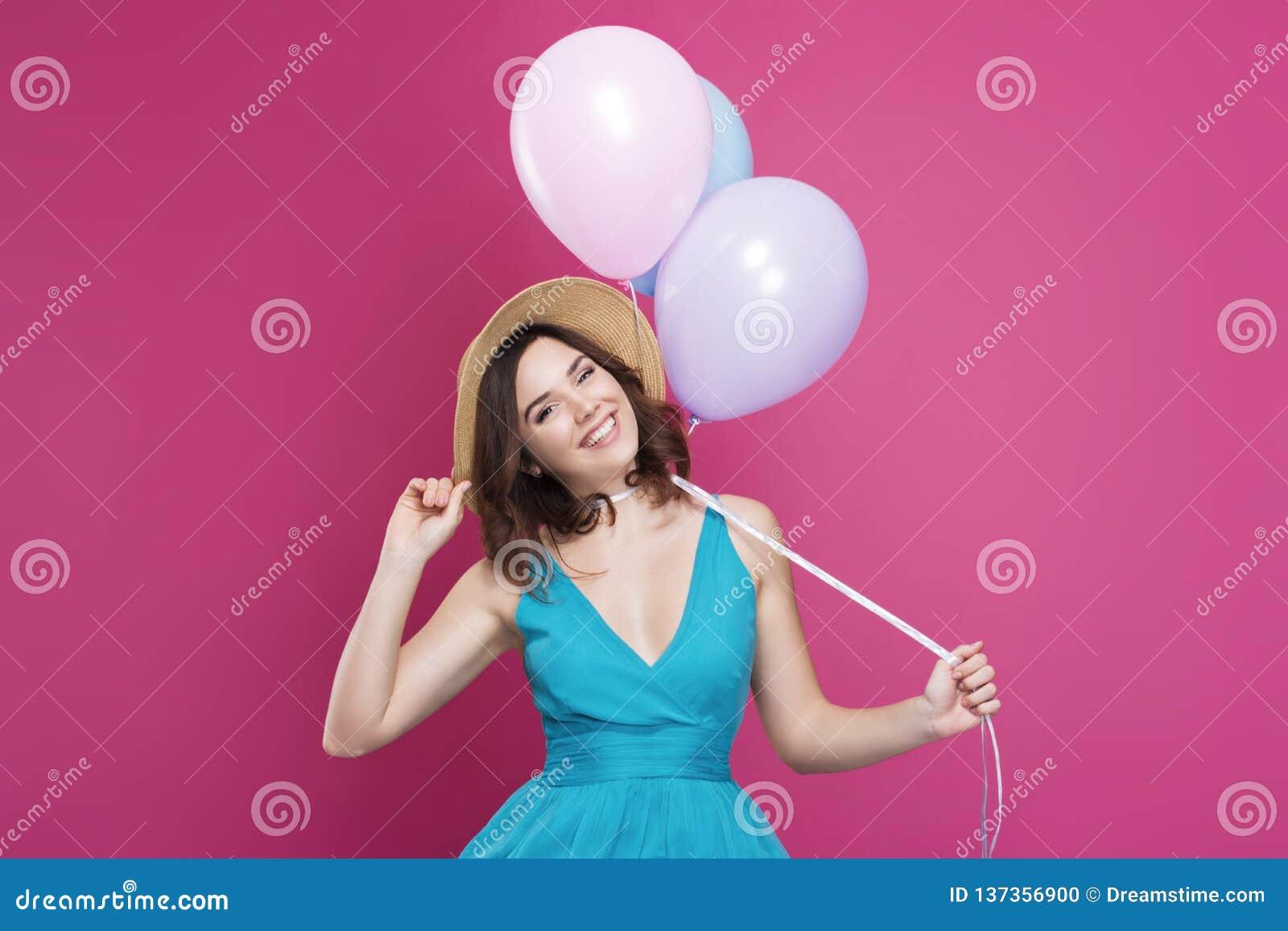 Piękna brunetka w błękitnej sukni słomianym kapeluszu i trzyma balony