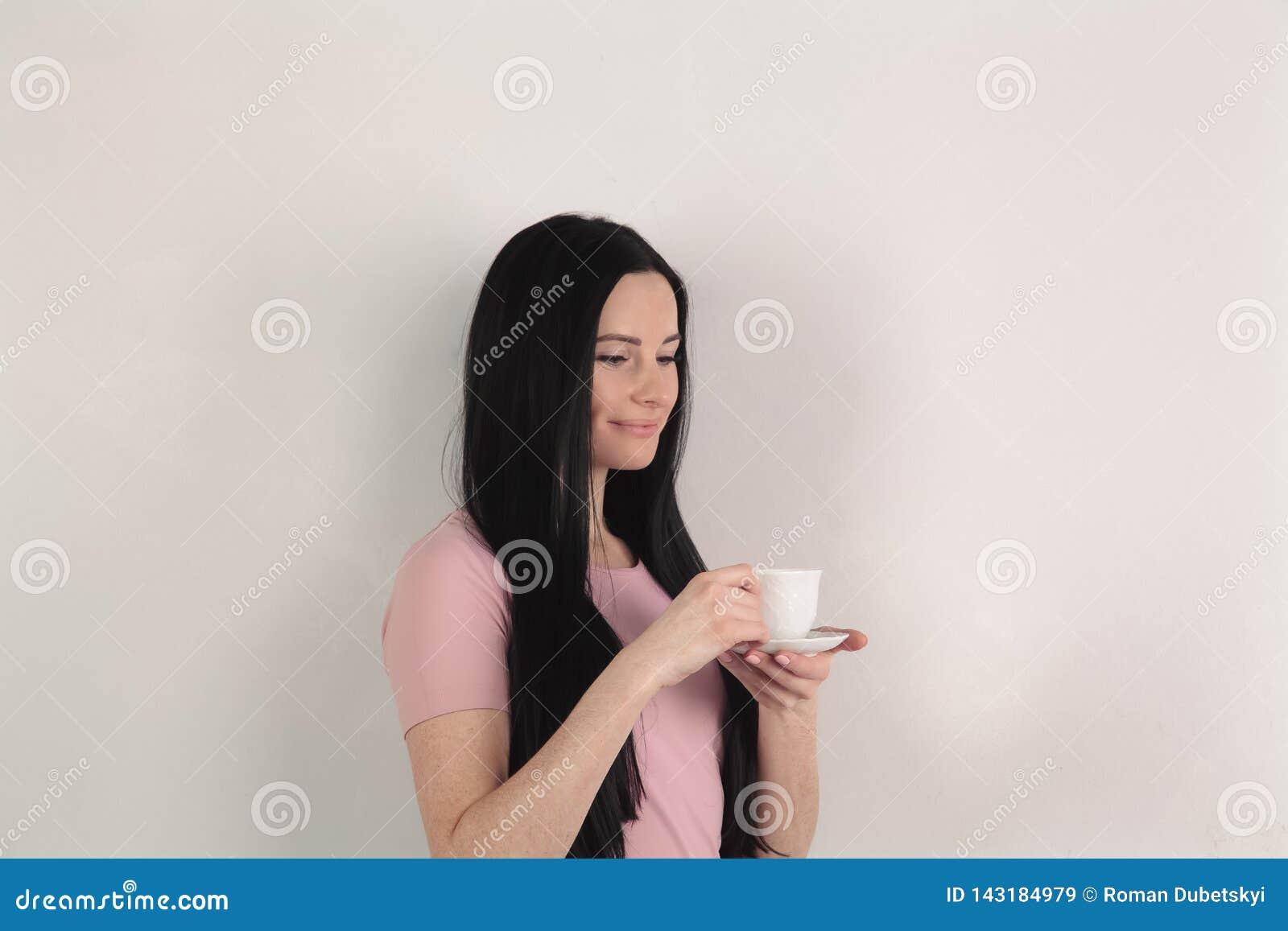 Piękna brunetka z długie włosy chwytami filiżanka kawy w jej rękach, stoi w profilu przeciw szaremu tłu