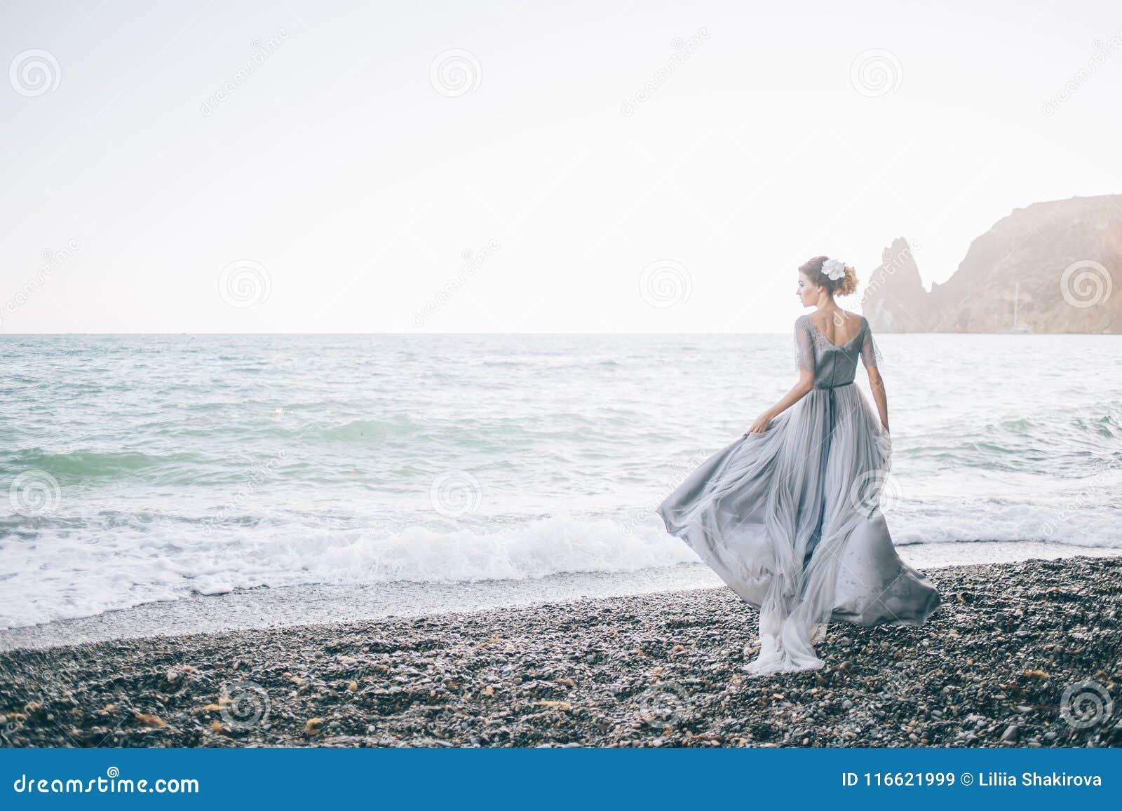 Piękna brunetki dziewczyna w długim popielatym cewieniu w wiatrowej sukni zrobi tiulowi chwyty z jeden ręką sukni spojrzenia prof