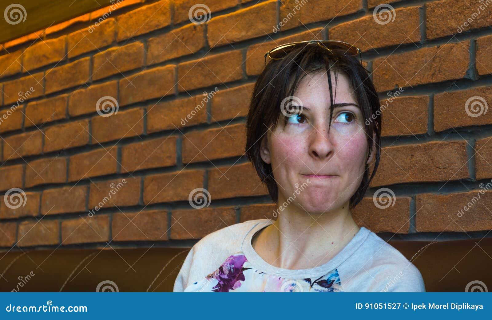 Piękna brunetki młoda kobieta siedzi przy bufetem z naciskać wargami