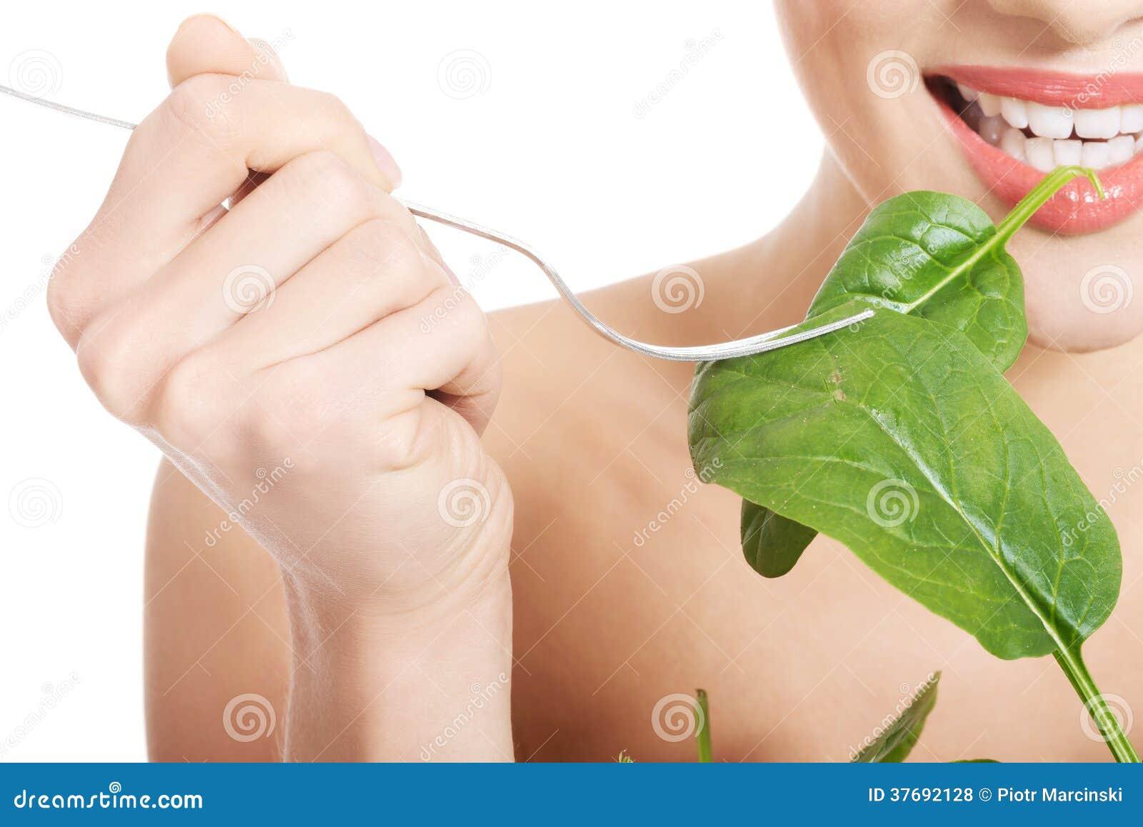 Piękna caucasian kobieta je świeżego zielonego luttce od pucharu