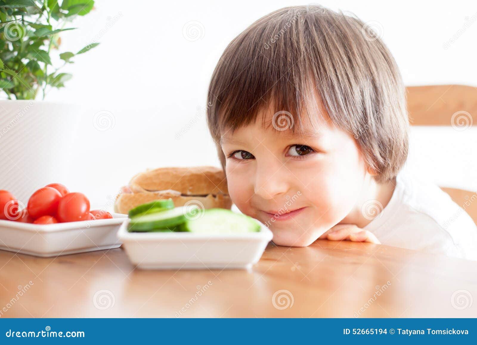 Piękna chłopiec, je kanapkę w domu, warzywa na