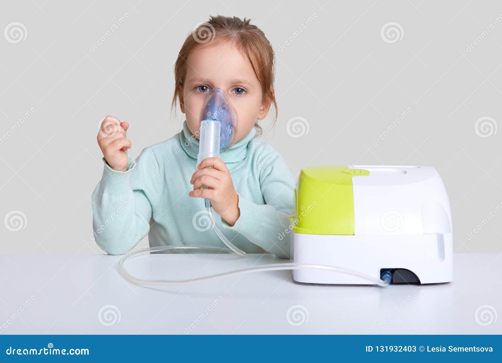 Piękna chora dziewczyna inhalacyjną terapię, używa przenośnego nebulizer, chwyty maskuje opary, siedzi przy białym desktop, odizo
