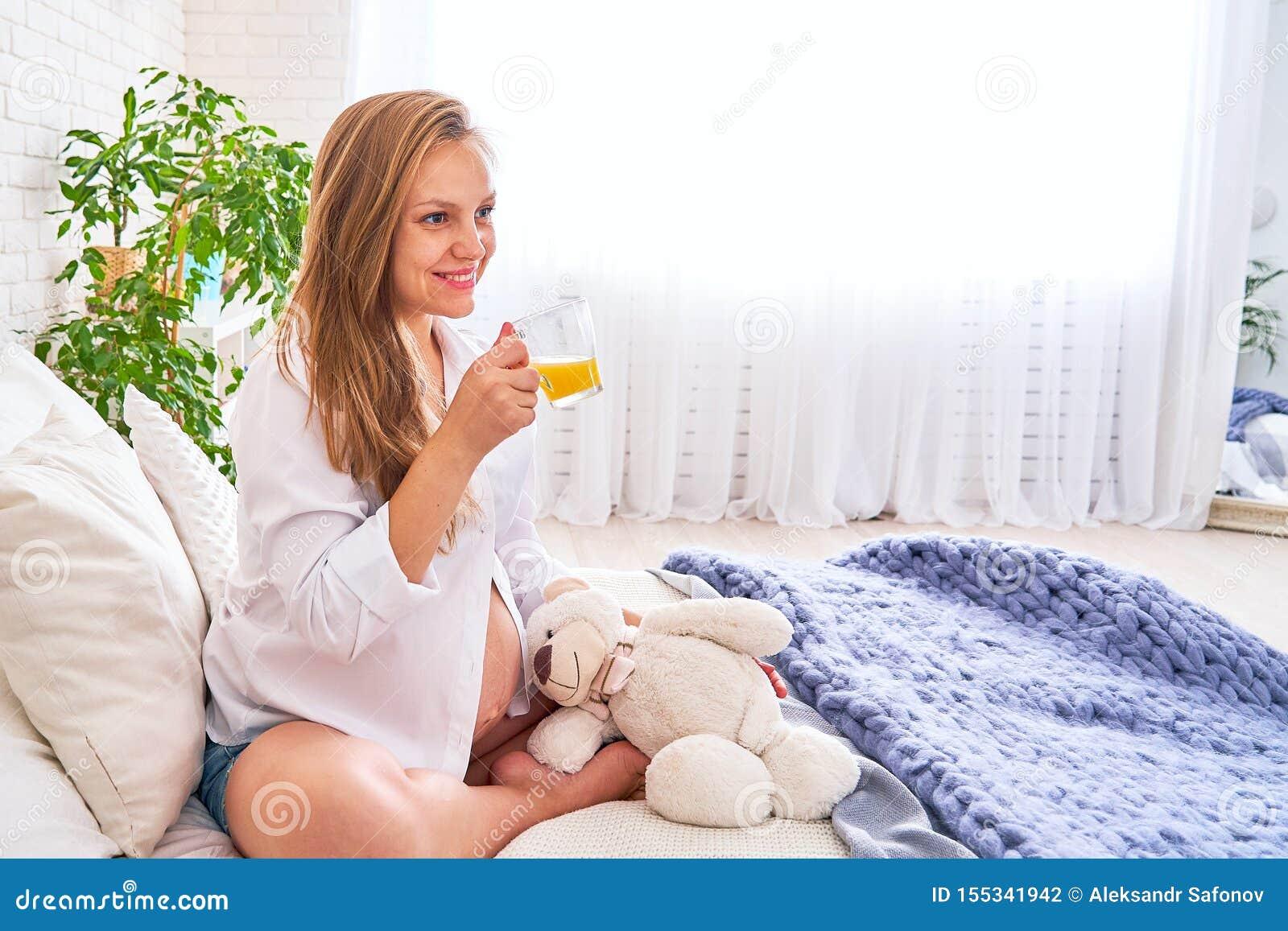 Piękna ciężarna blondynki kobieta siedzi na łóżku w jaskrawej sypialni dziewczyna na wielkiego terminu ciążowego popijania owocow