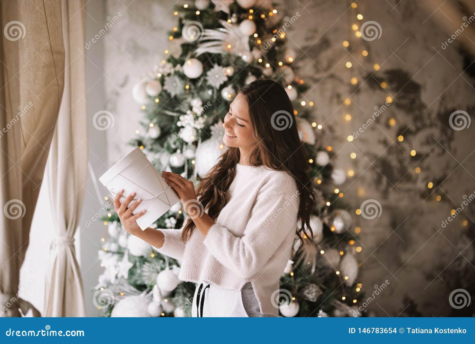 Piękna ciemnowłosa dziewczyna ubierał w białych puloweru i spodń stojakach obok okno na tle Nowy