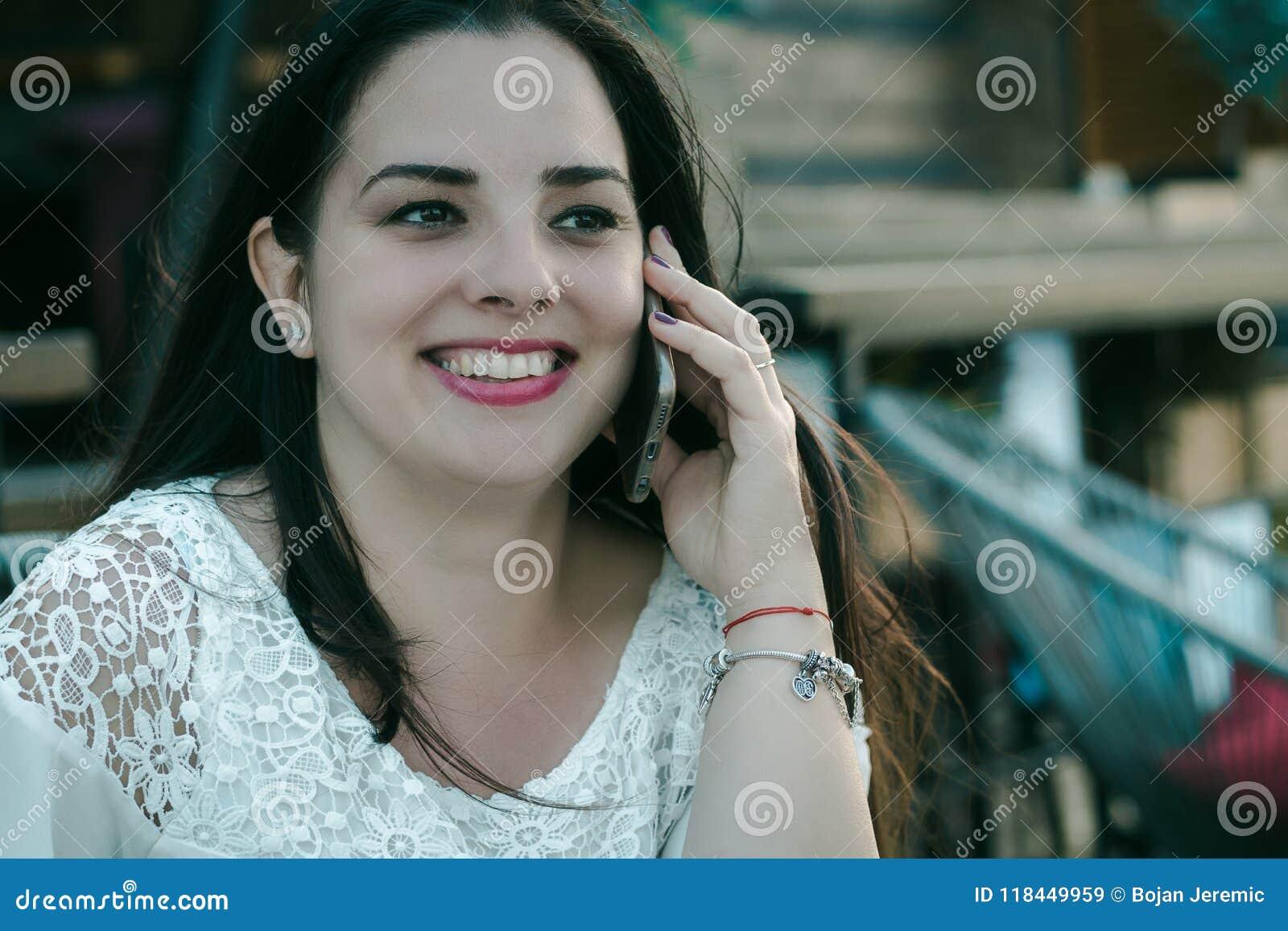 Piękna czarni włosy dziewczyna opowiada na telefonie
