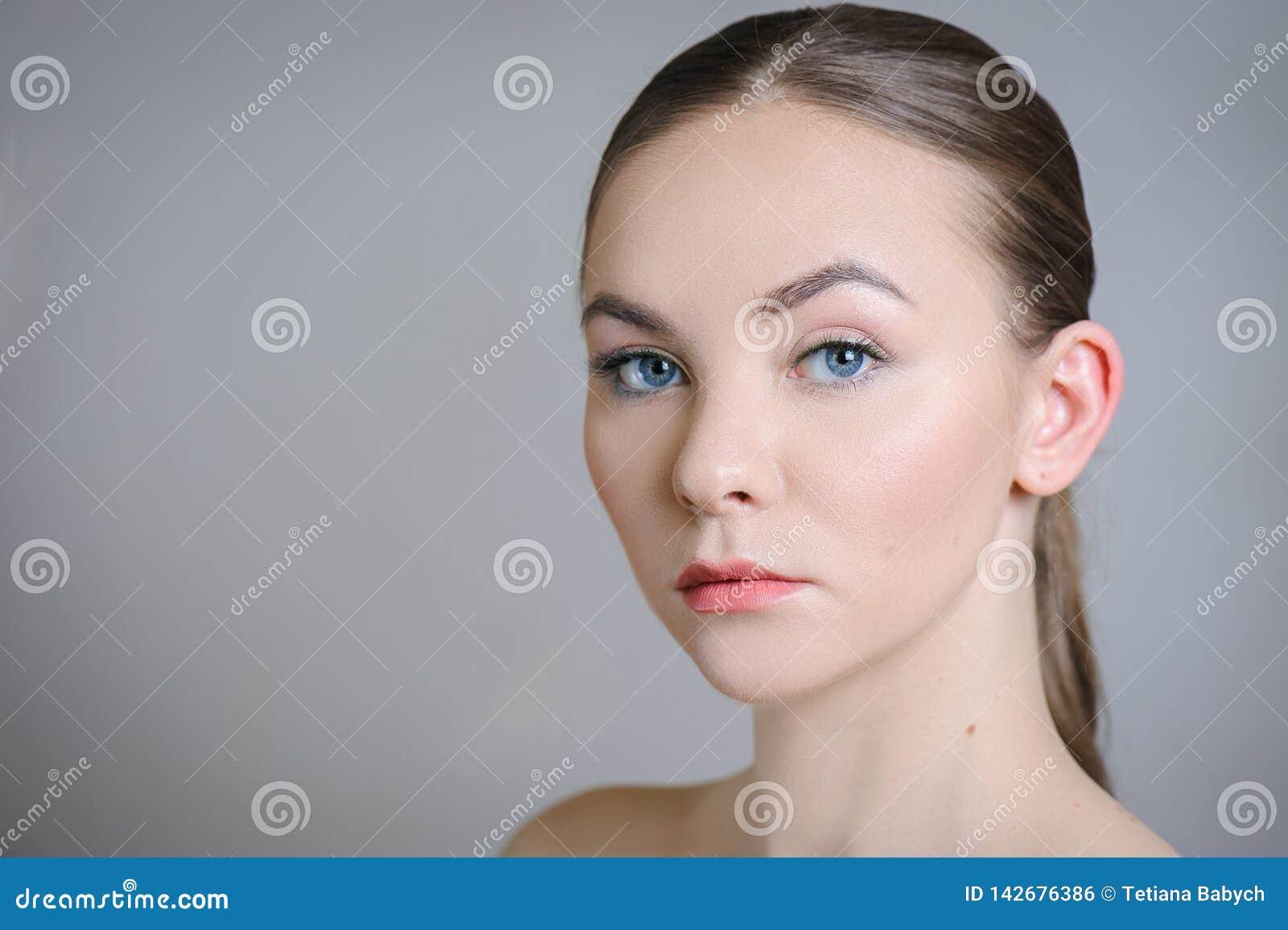 Piękna dorosła dziewczyna pozuje z nagim makeup z czystą skórą i dba jej skórę