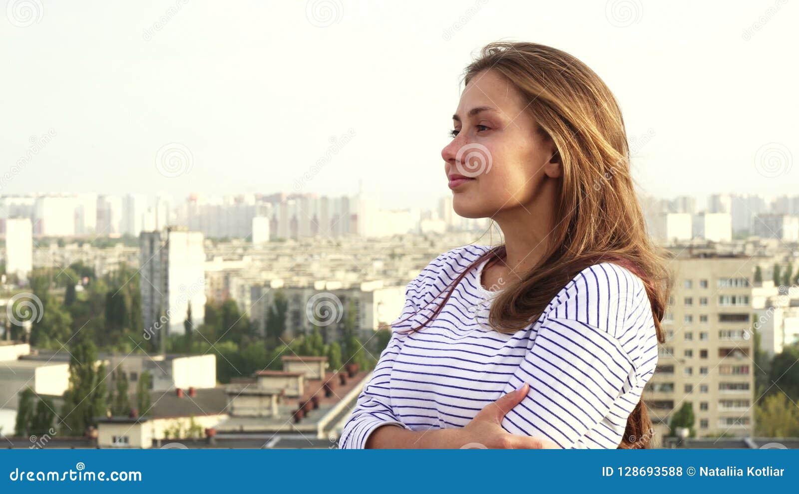 Piękna dziewczyna cieszy się widzieć od dachu miasto
