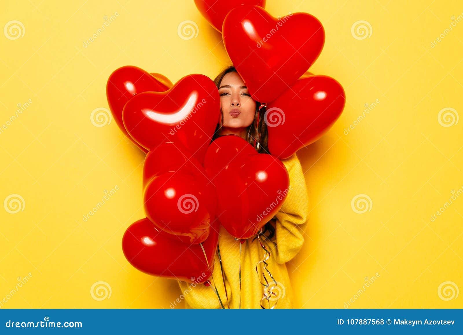Piękna dziewczyna daje buziakowi patrzeje z serca kształtował lotniczych balony