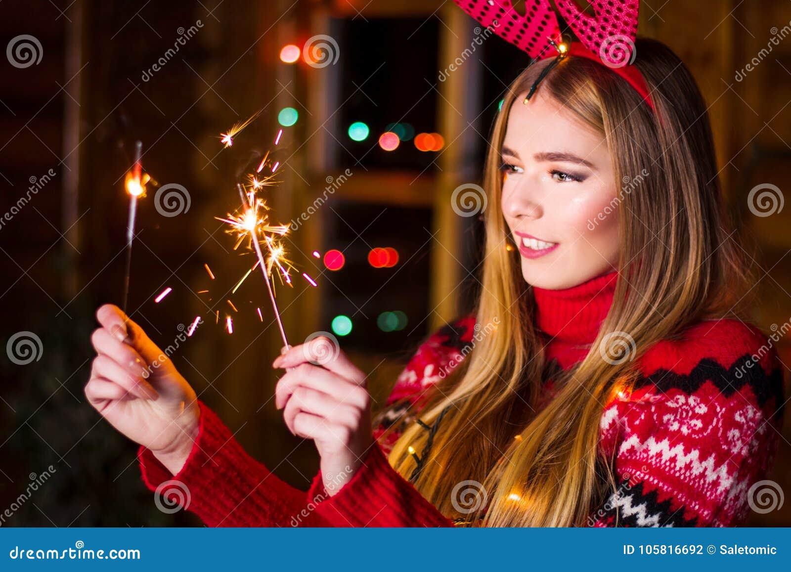 Piękna dziewczyna jest ubranym czerwonego pulower z świątecznymi światłami