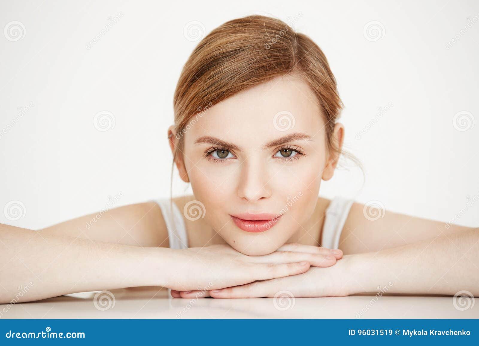 Piękna dziewczyna ono uśmiecha się z perfect czystą skórą patrzejący kamery obsiadanie przy stołem nad białym tłem Piękno zdrój i