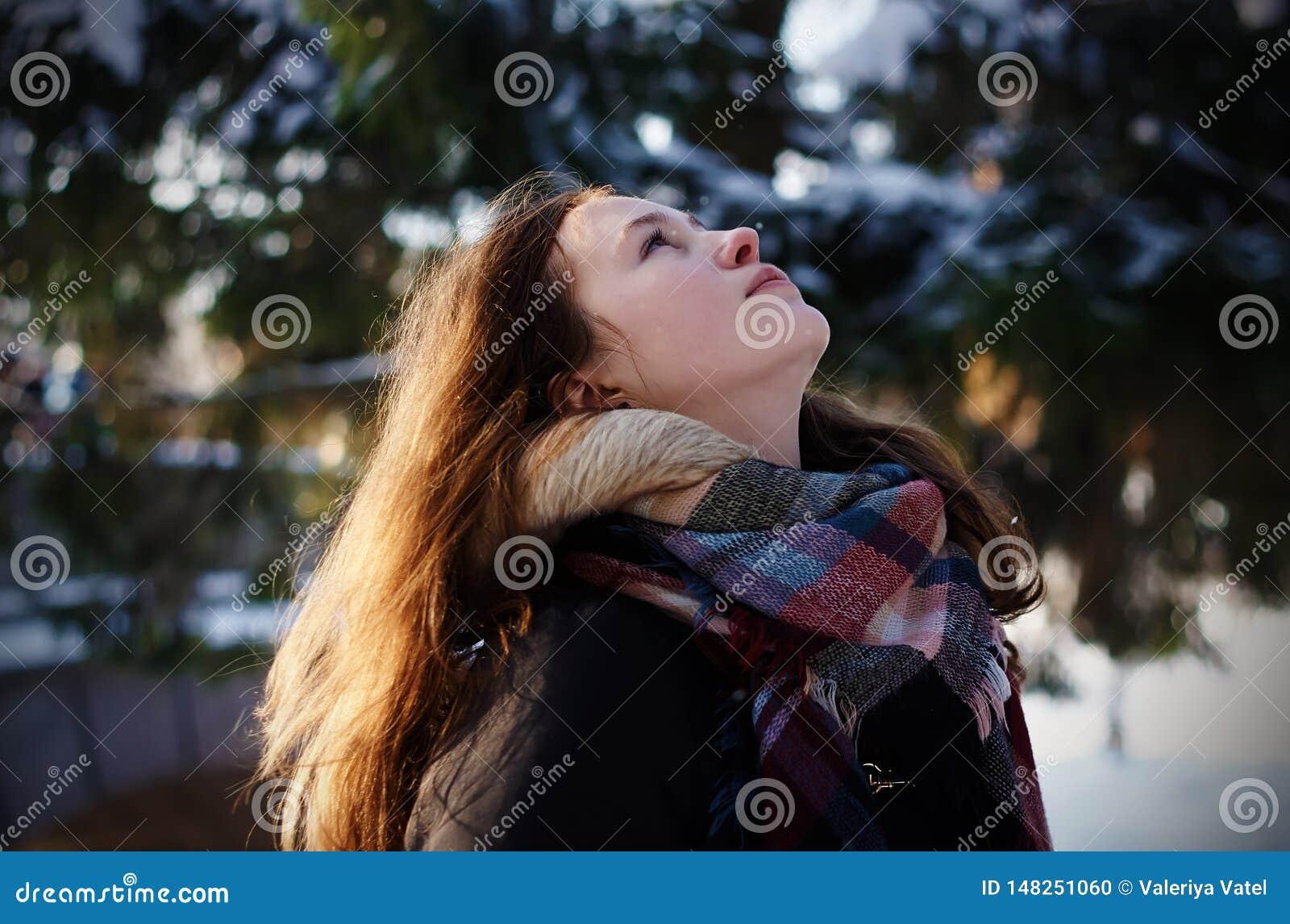 Piękna dziewczyna patrzeje niebo pozycję w zimy pogodzie w lesie