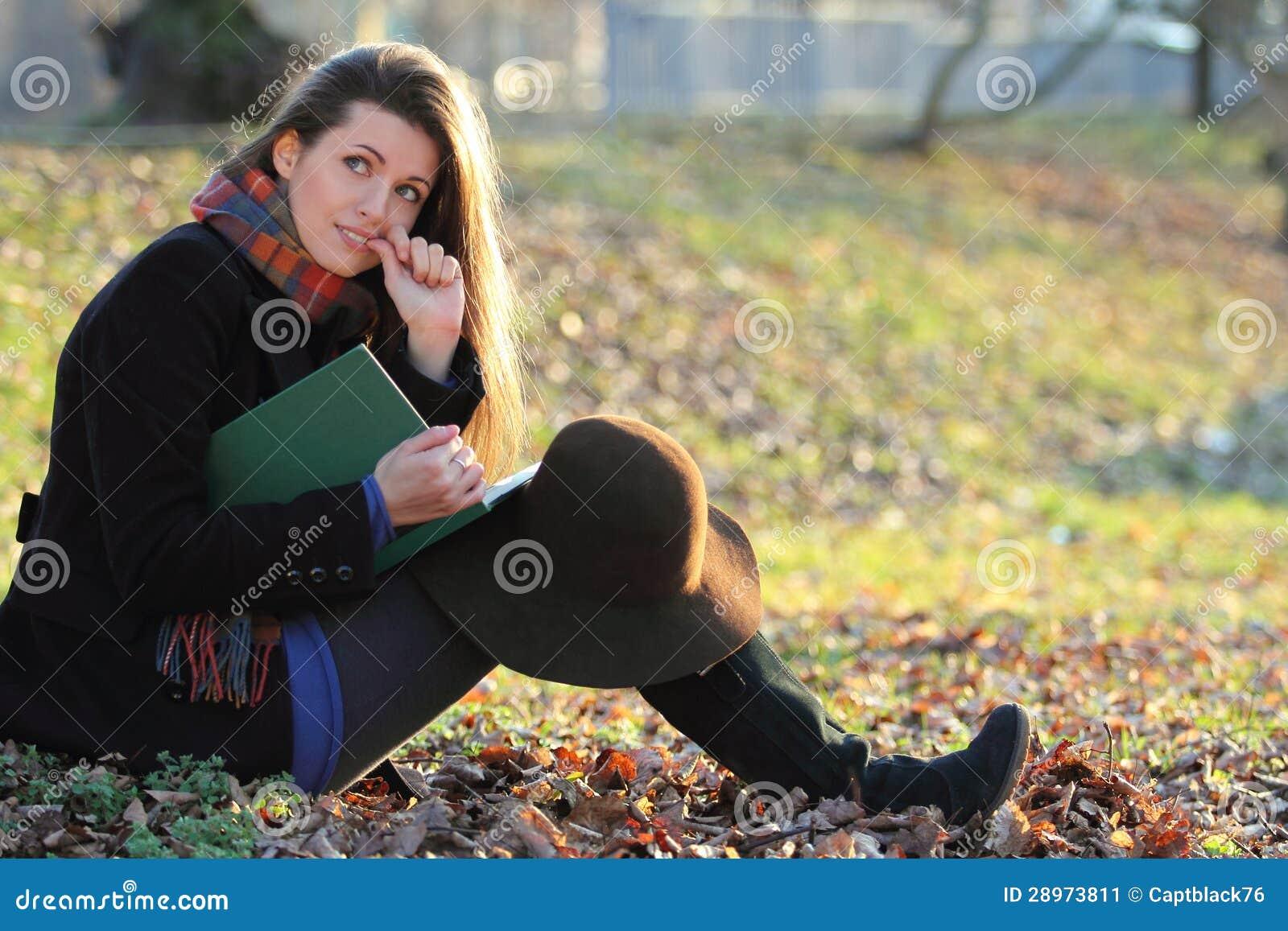Piękna dziewczyna studiuje książkę przy parkiem