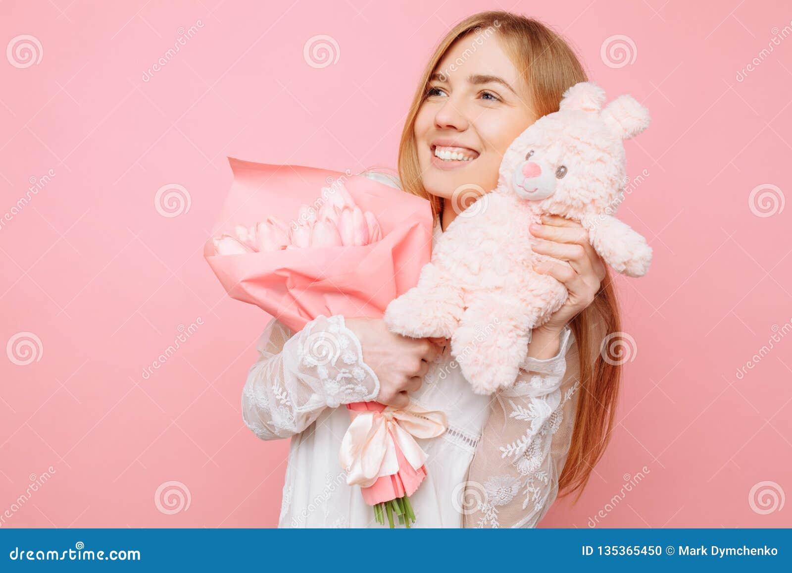 Piękna dziewczyna trzyma miś pluszowy zając i bukieta tulipany w jej rękach na różowym tle, to walentynki dni