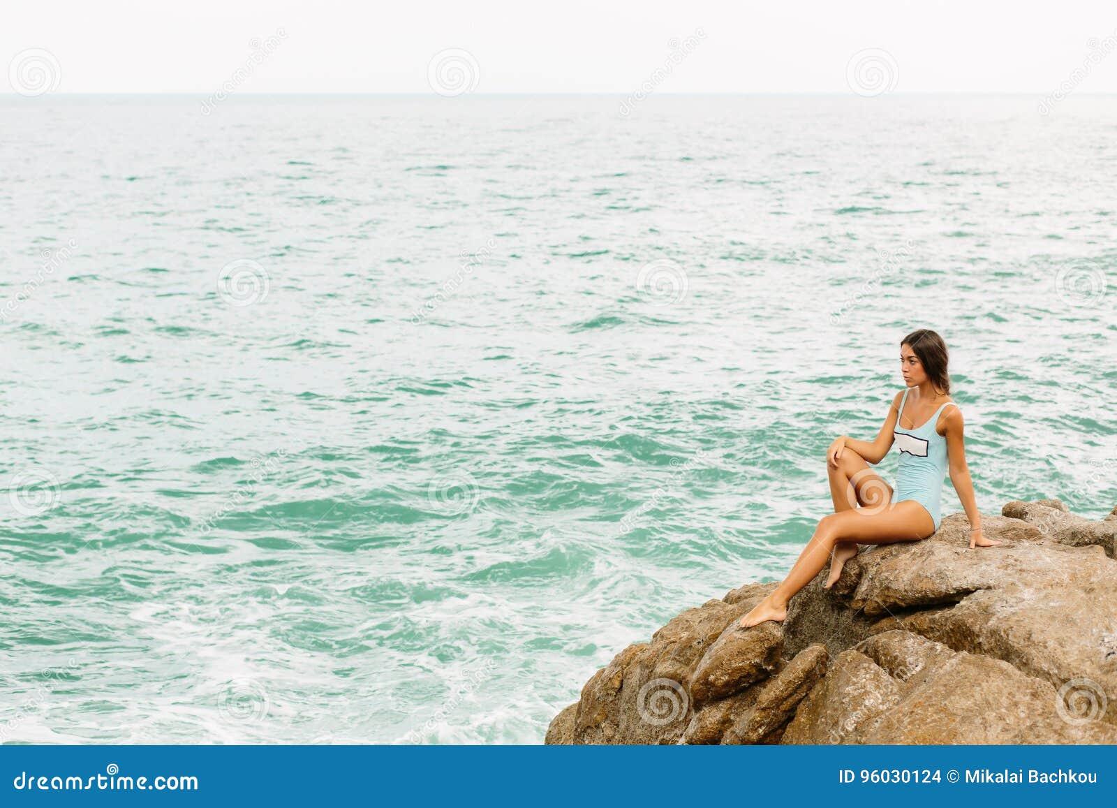 Piękna dziewczyna w błękitnym swimsuit siedzi na dużym kamieniu