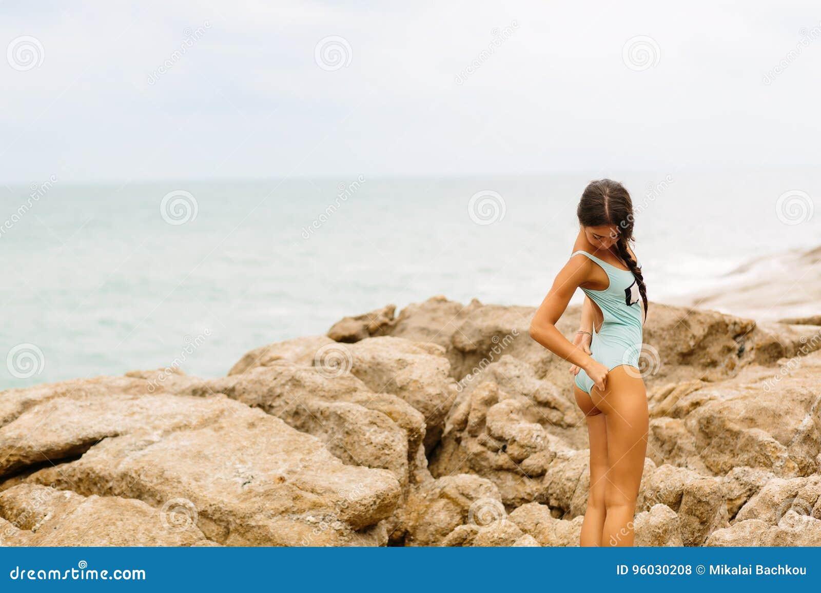 Piękna dziewczyna w błękitnym swimsuit spacerze na dużym kamieniu