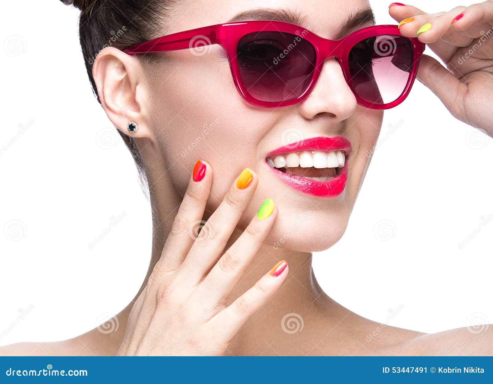 Piękna dziewczyna w czerwonych okularach przeciwsłonecznych z jaskrawym makeup i kolorowymi gwoździami Piękno Twarz