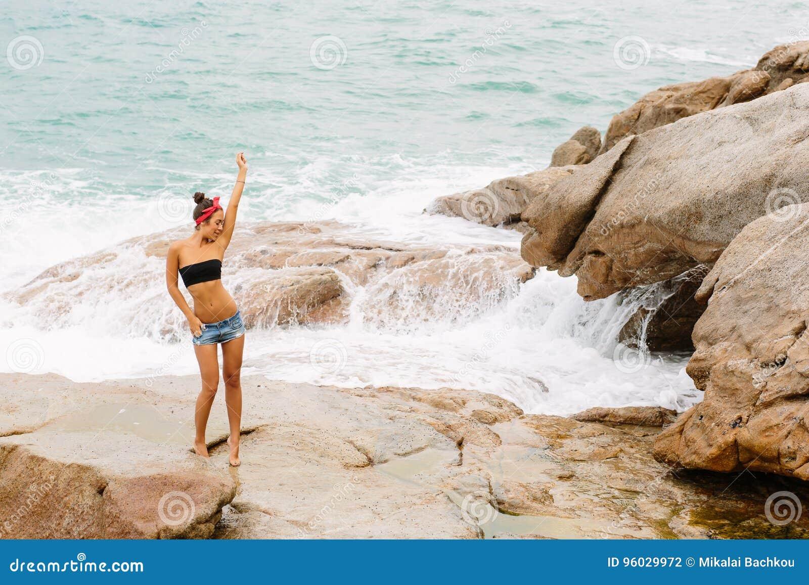 Piękna dziewczyna w krótkich skrótach chodzi na dużych kamieniach