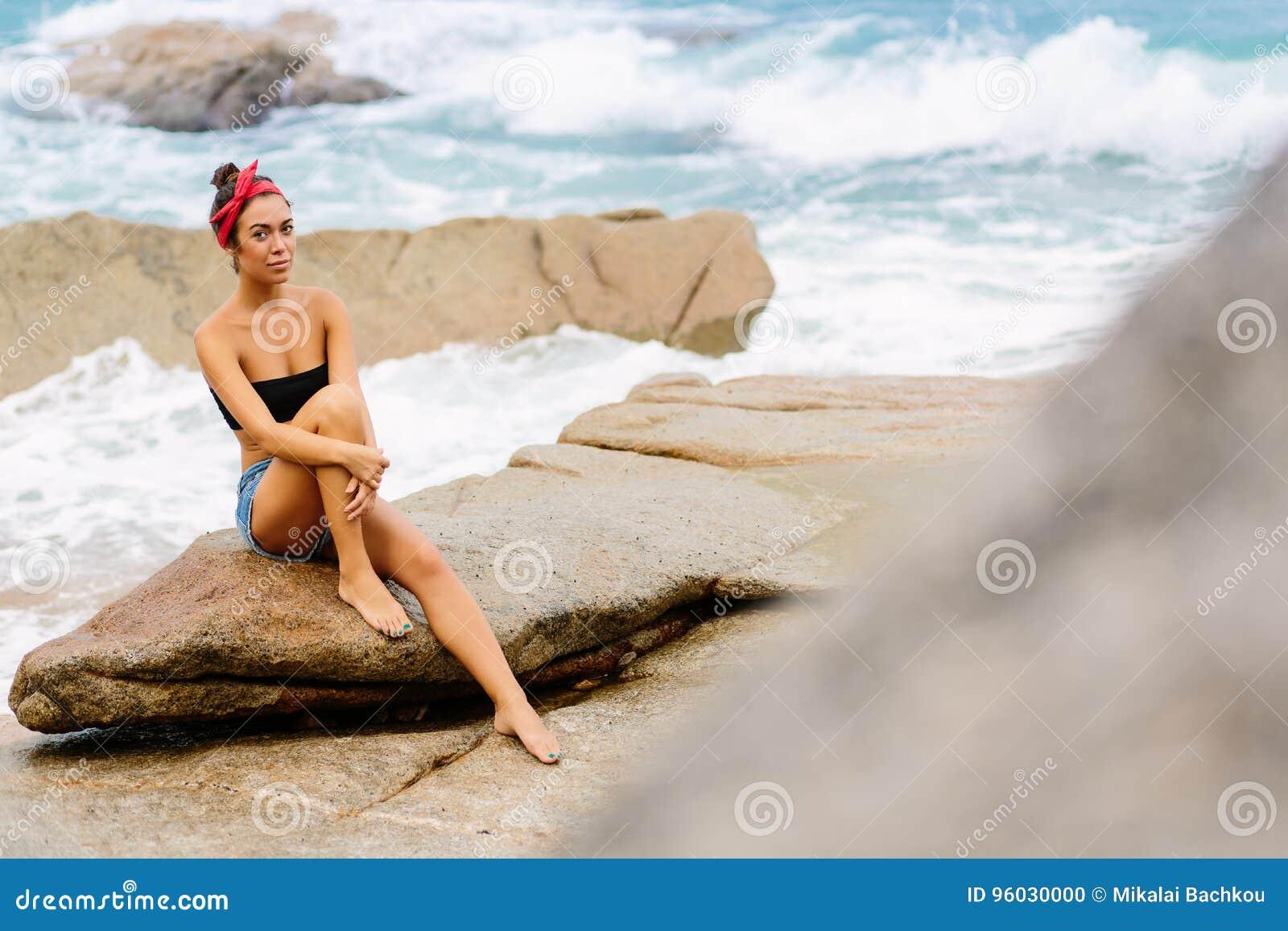 Piękna dziewczyna w krótkich skrótach siedzi na dużych kamieniach