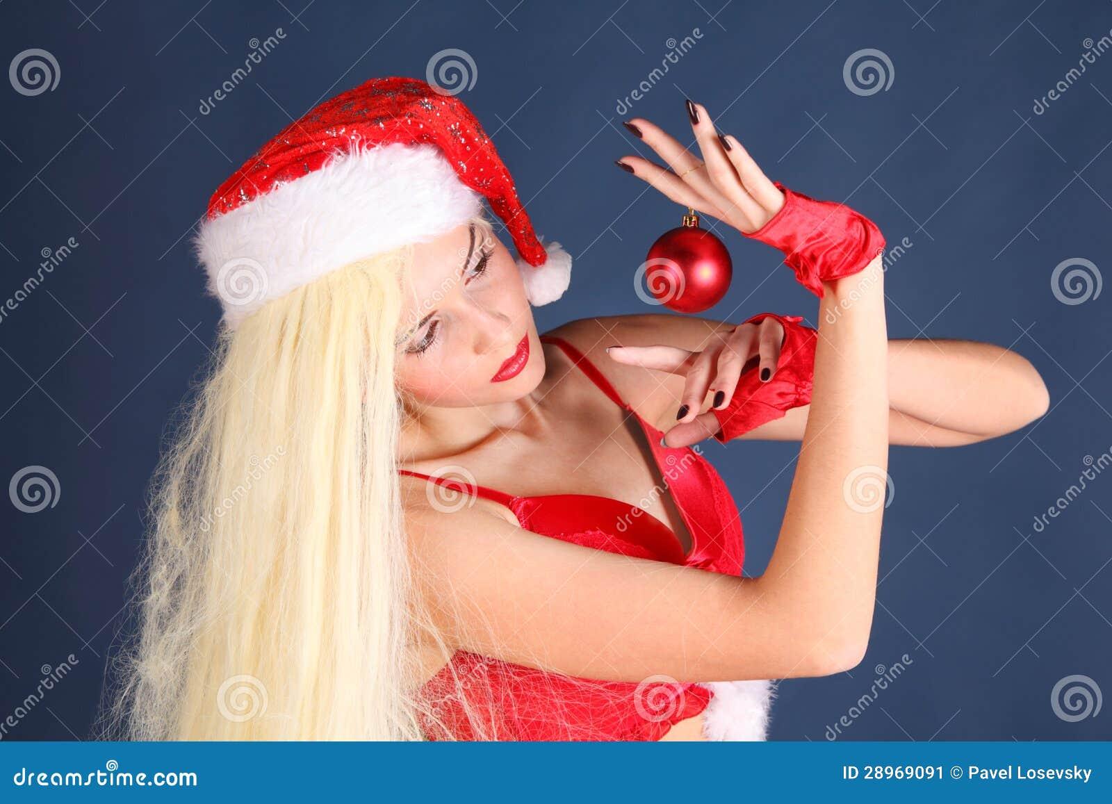 Piękna dziewczyna w seksownym nowego roku kostiumu trzyma Bożenarodzeniową piłkę