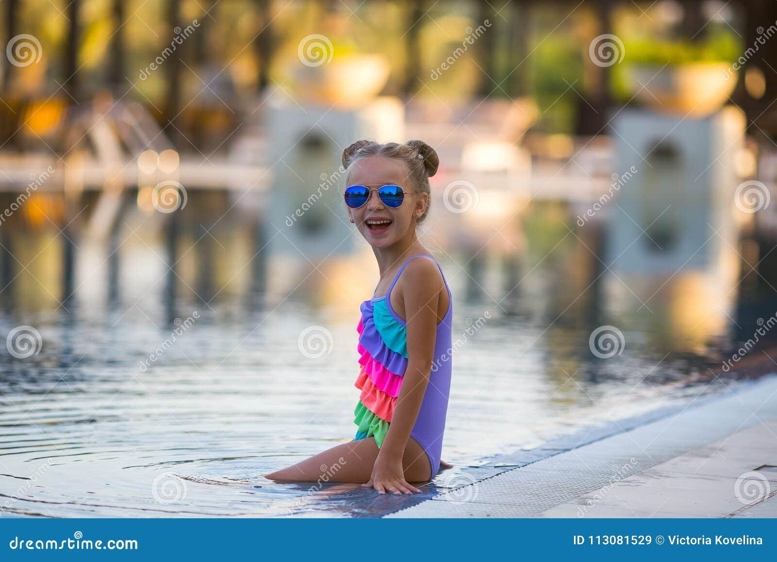 Piękna dziewczyna w swimsuit pływa w basenie latem