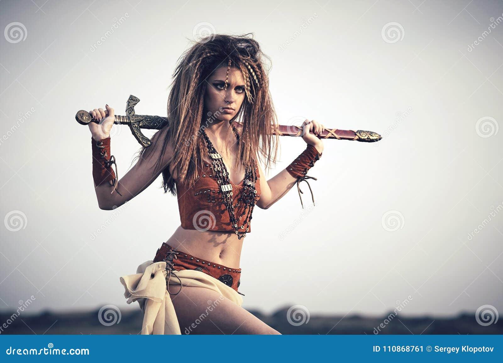Piękna dziewczyna w ubraniach amazonka z swor lub Viking,