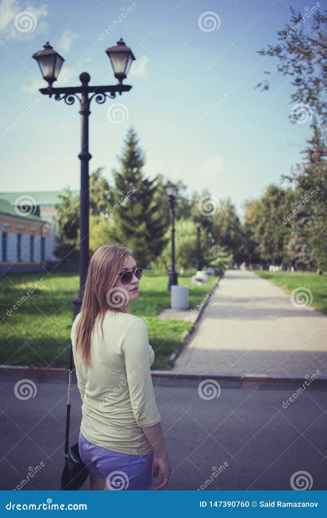 Piękna dziewczyna z bieżącym włosy w krótkich skrótach i szkłach na tle asfaltowa ścieżka z lampionem