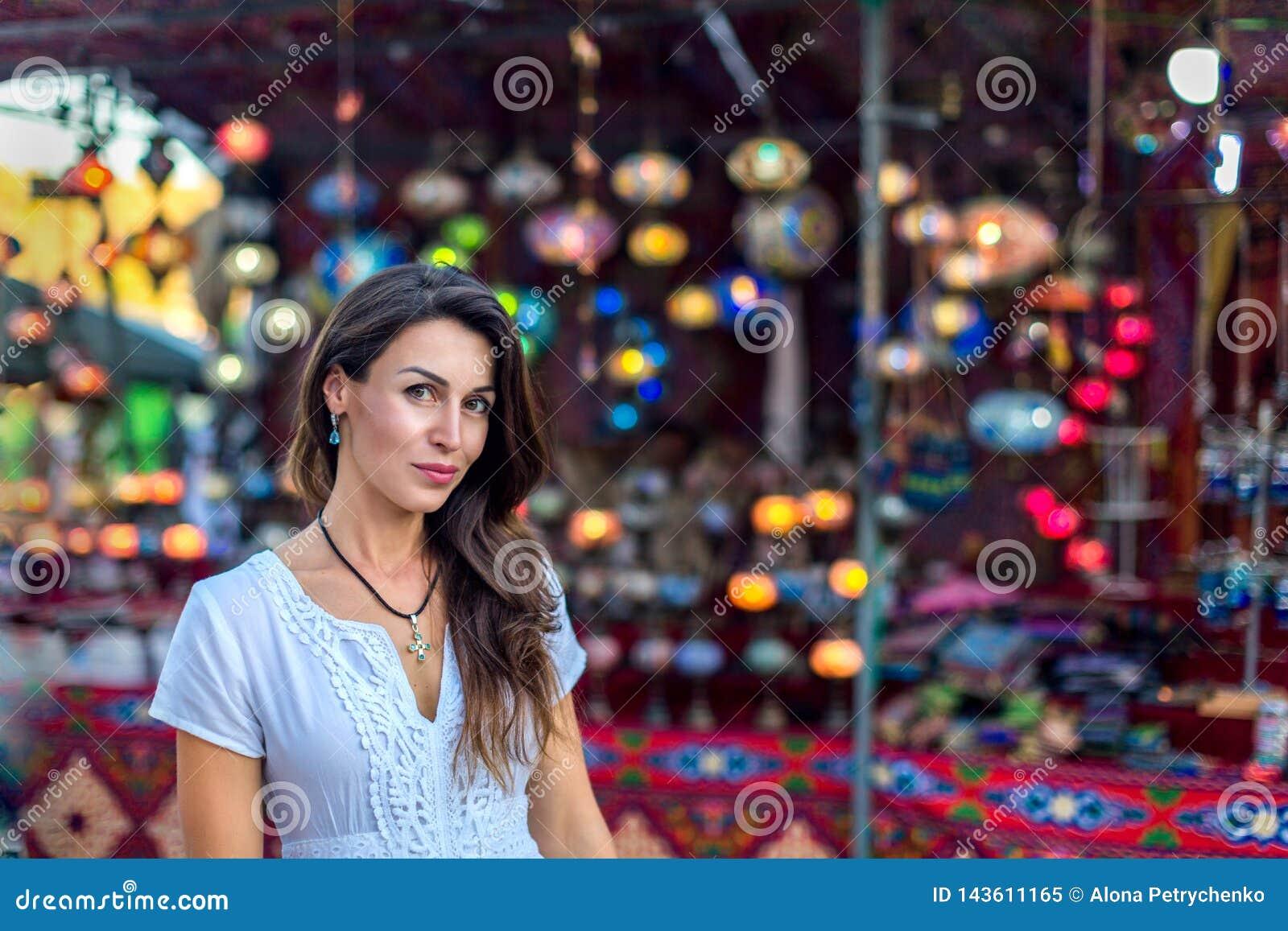 Piękna dziewczyna z długie włosy w białej sukni na tle jarzyć się orientalne marokańskie etniczne lampy przy jarmarku rynkiem
