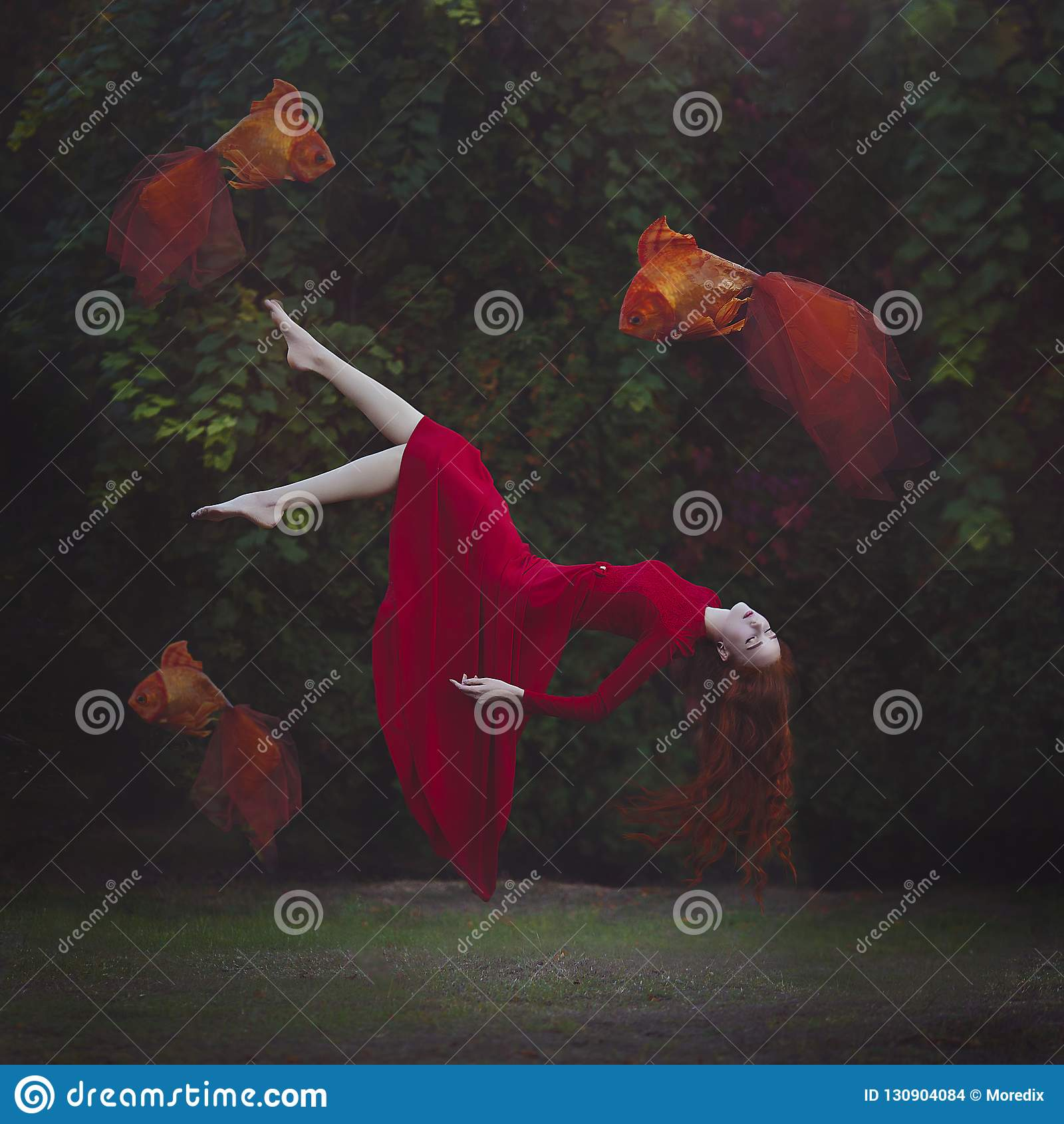 Piękna dziewczyna z długim czerwonym włosy w czerwonej sukni levitating nad ziemia Surrealistyczna magiczna fotografia kobieta z