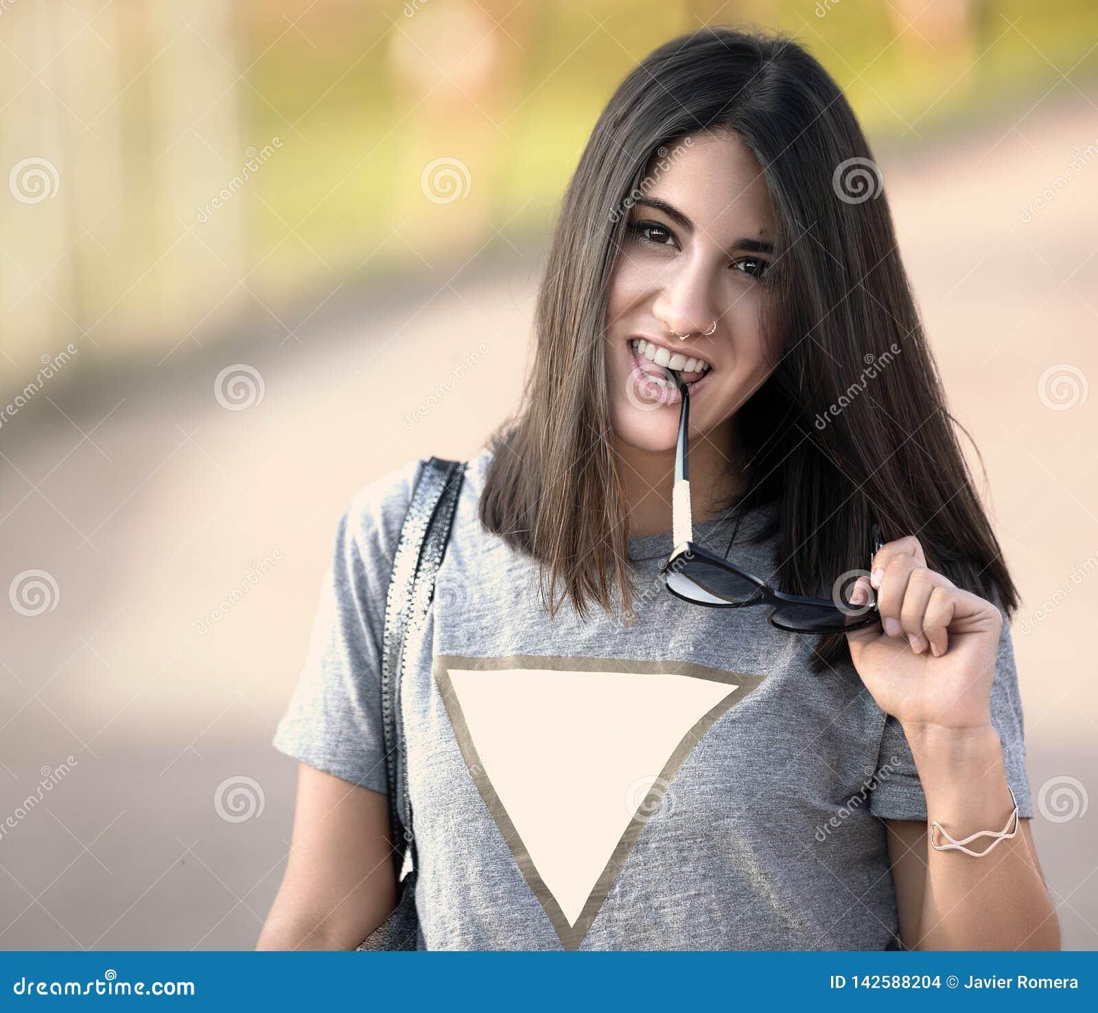 Piękna dziewczyna z jej okularami przeciwsłonecznymi w ona ręka