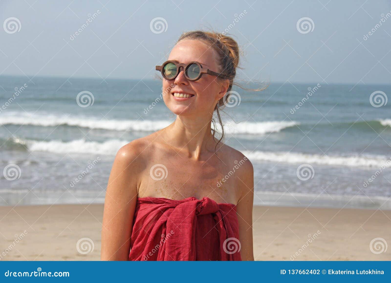 Piękna dziewczyny pokraka w czerwonym blondynie na tle morze i sukni, Lato dziewczyna w round drewnianych szkłach niezwykły