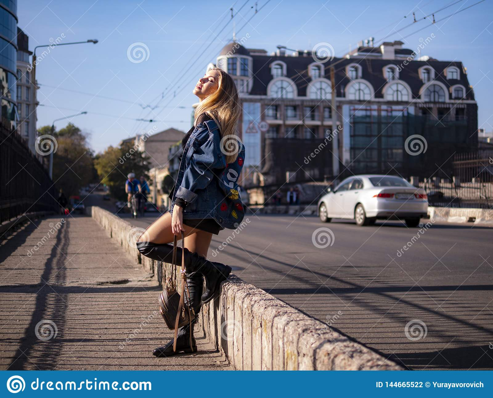 Piękna elegancka nastolatek dziewczyna z bieżącym włosy w pełnym przyroscie na miasto moście