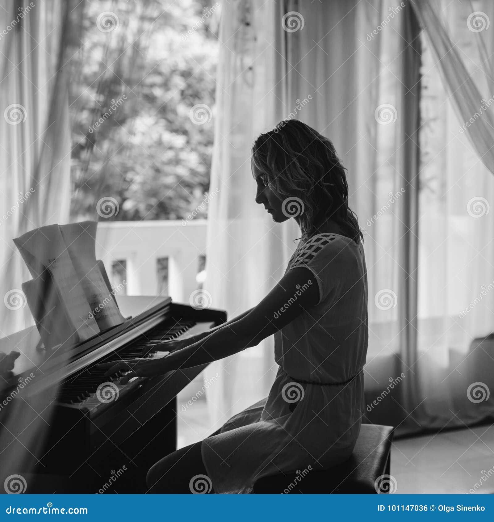 Piękna fortepianowa bawić się kobieta czarny white