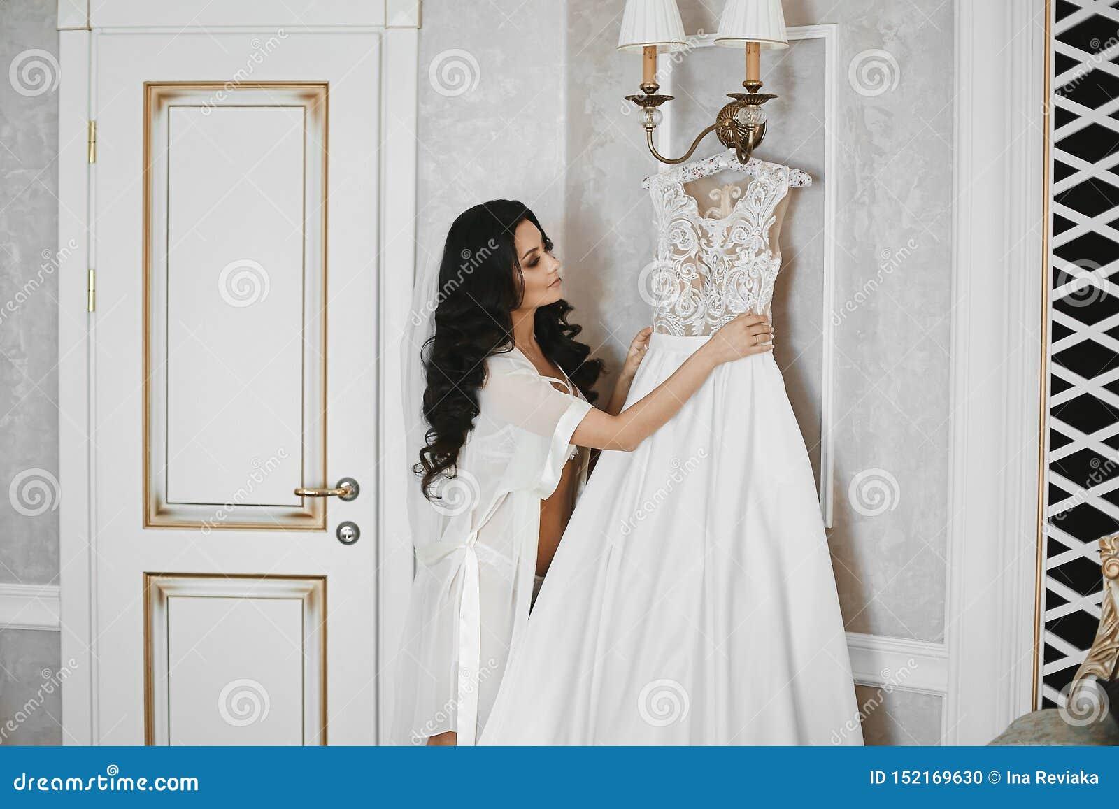Piękna i seksowna brunetka modela dziewczyna z doskonalić ciałem w uwodzicielskim peignoir, patrzeje na jej ślubnej sukni przedte