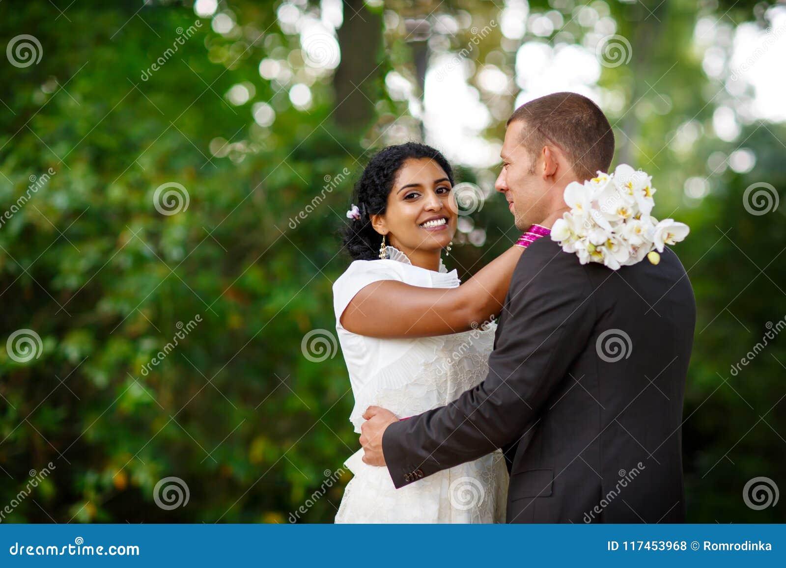 Piękna indyjska panna młoda i caucasian fornal w lato parku, kwitnie szczęśliwych mienia kobiety potomstwa Młody człowiek ono uśm