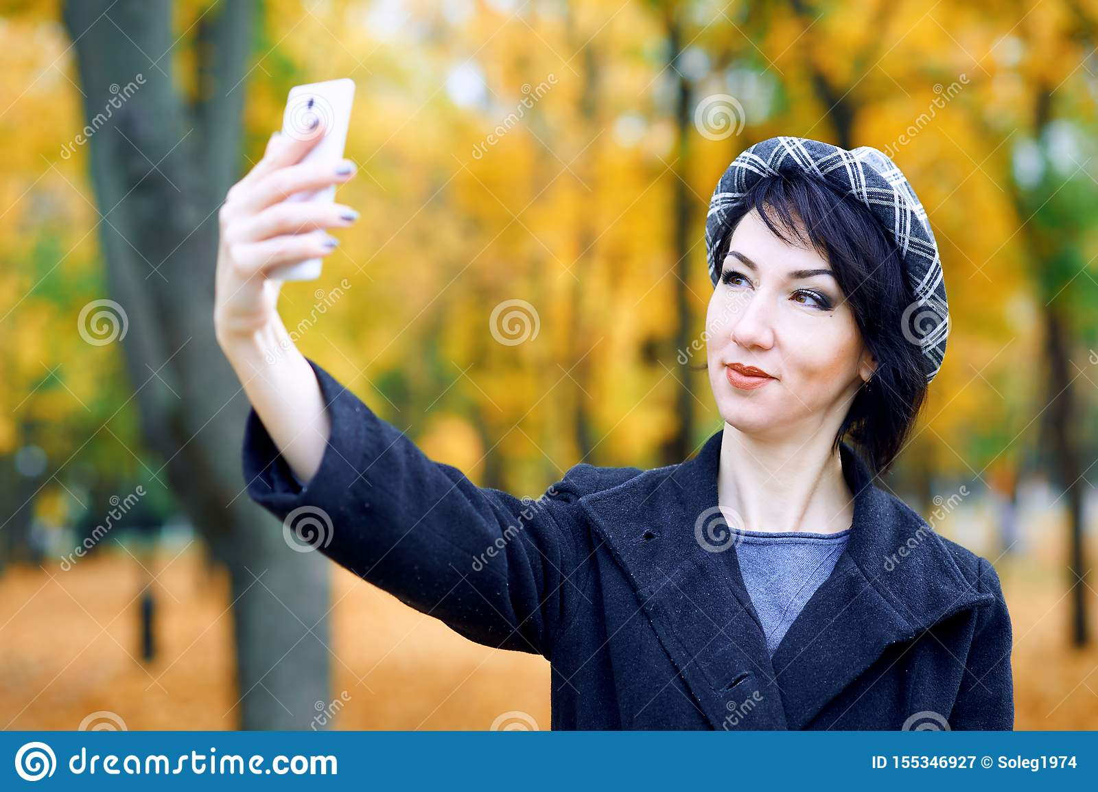 Piękna kobieta bierze selfie smartphone i ma zabawę w jesieni miasta parku, sezon jesienny, kolor żółty opuszcza