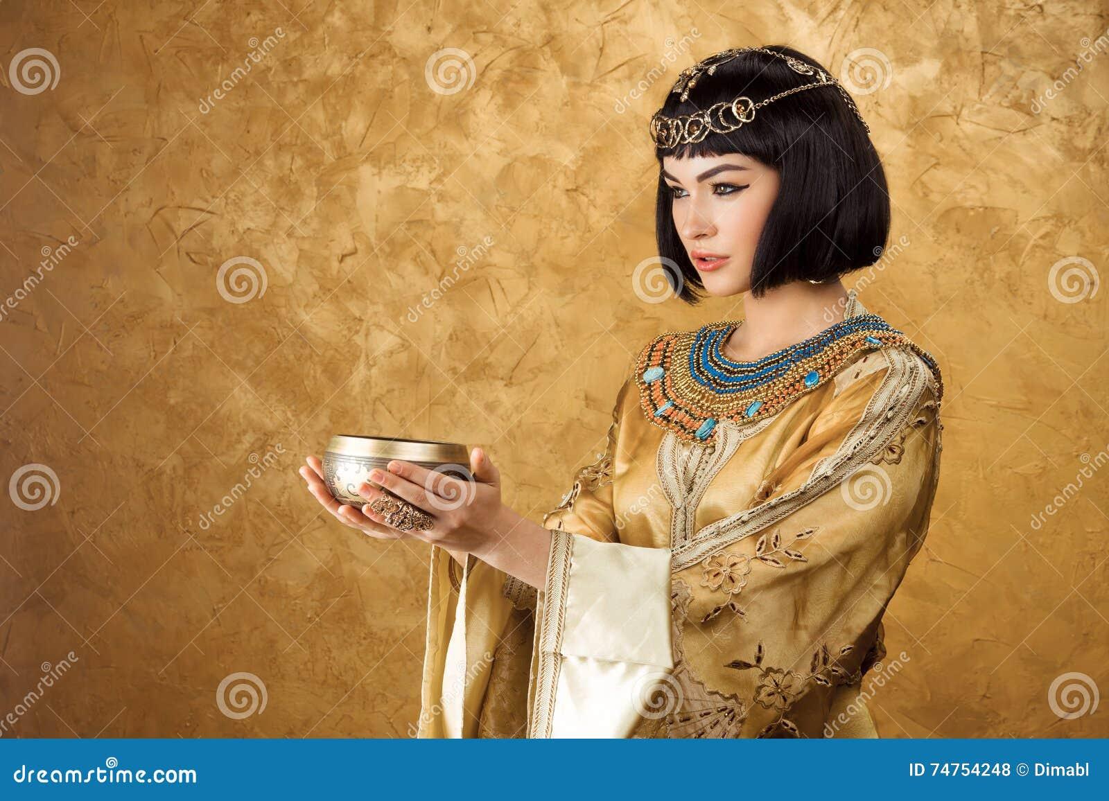Piękna kobieta lubi Egipskiej królowej Cleopatra z filiżanką na złotym tle