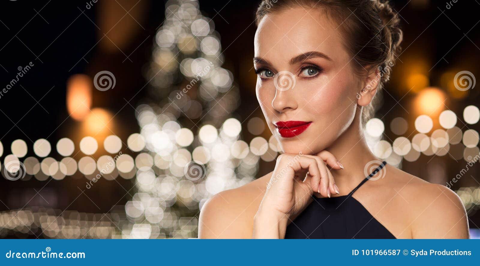 Piękna kobieta nad choinek światłami