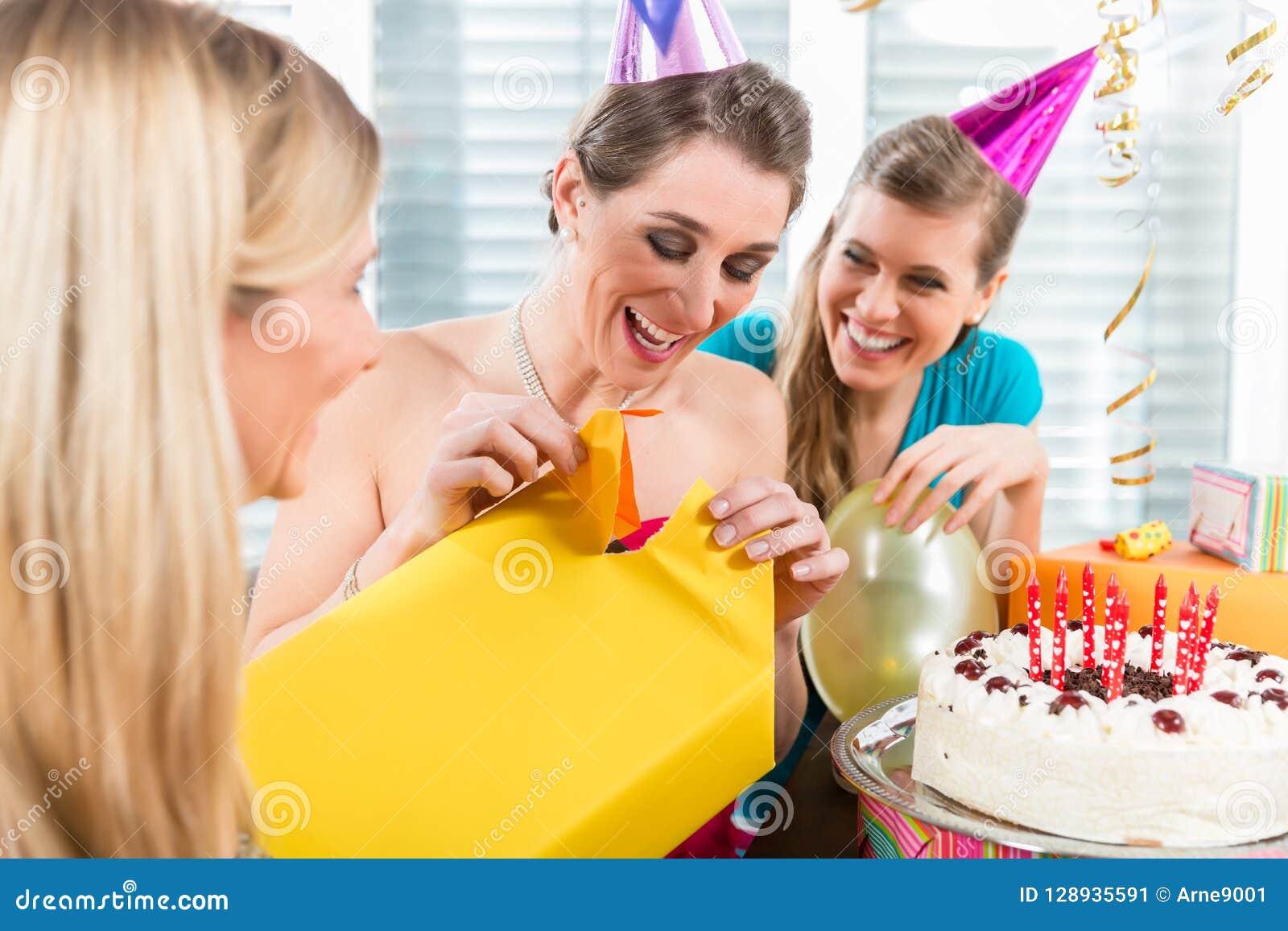 Piękna kobieta otwiera prezenta pudełko podczas gdy świętujący jej birthda