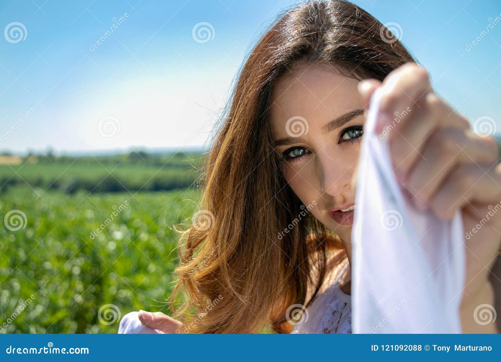 Piękna kobieta, panna młoda z niebieskimi oczami i brown włosy, chodzimy przez uprawy pola na pogodnym lata ` s dniu