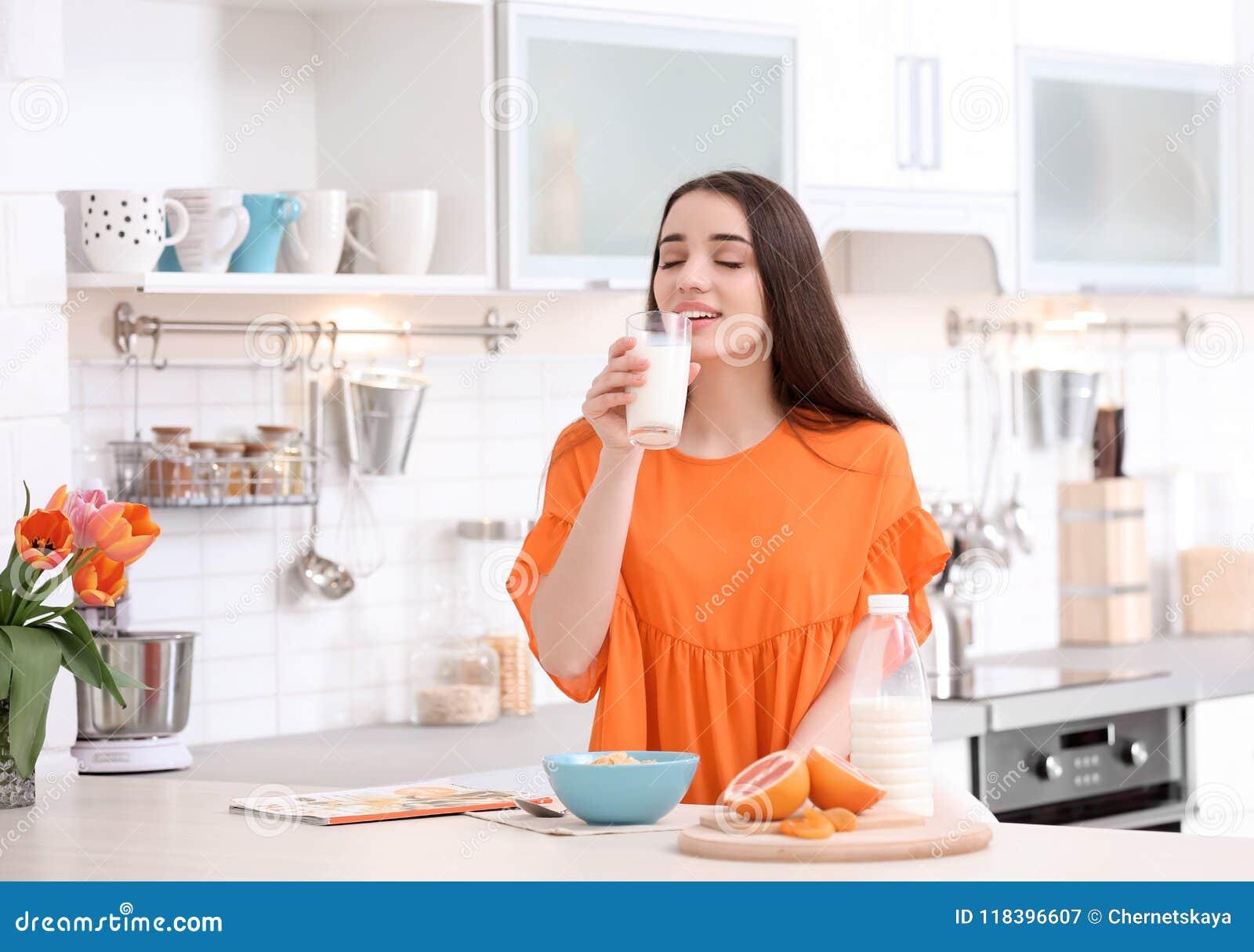Piękna kobieta pije mleko w kuchni