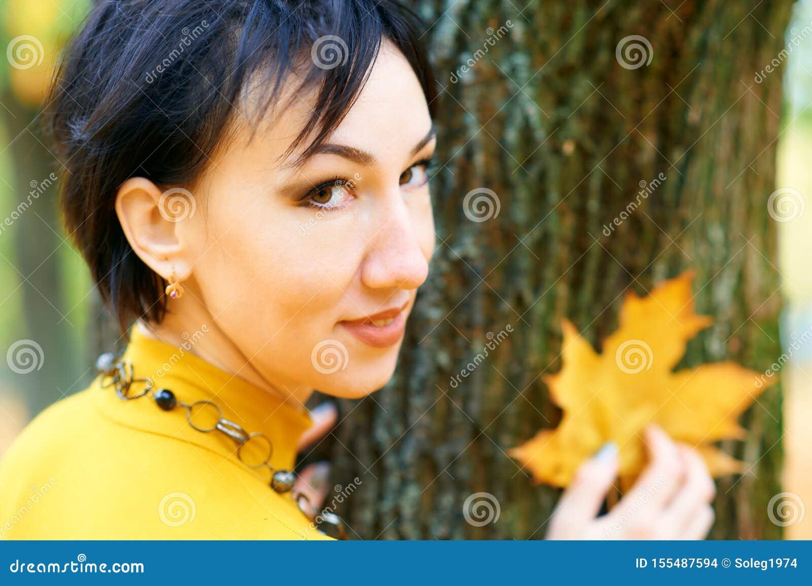 Piękna kobieta pozuje z żółtymi liśćmi w jesieni miasta parku, sezon jesienny