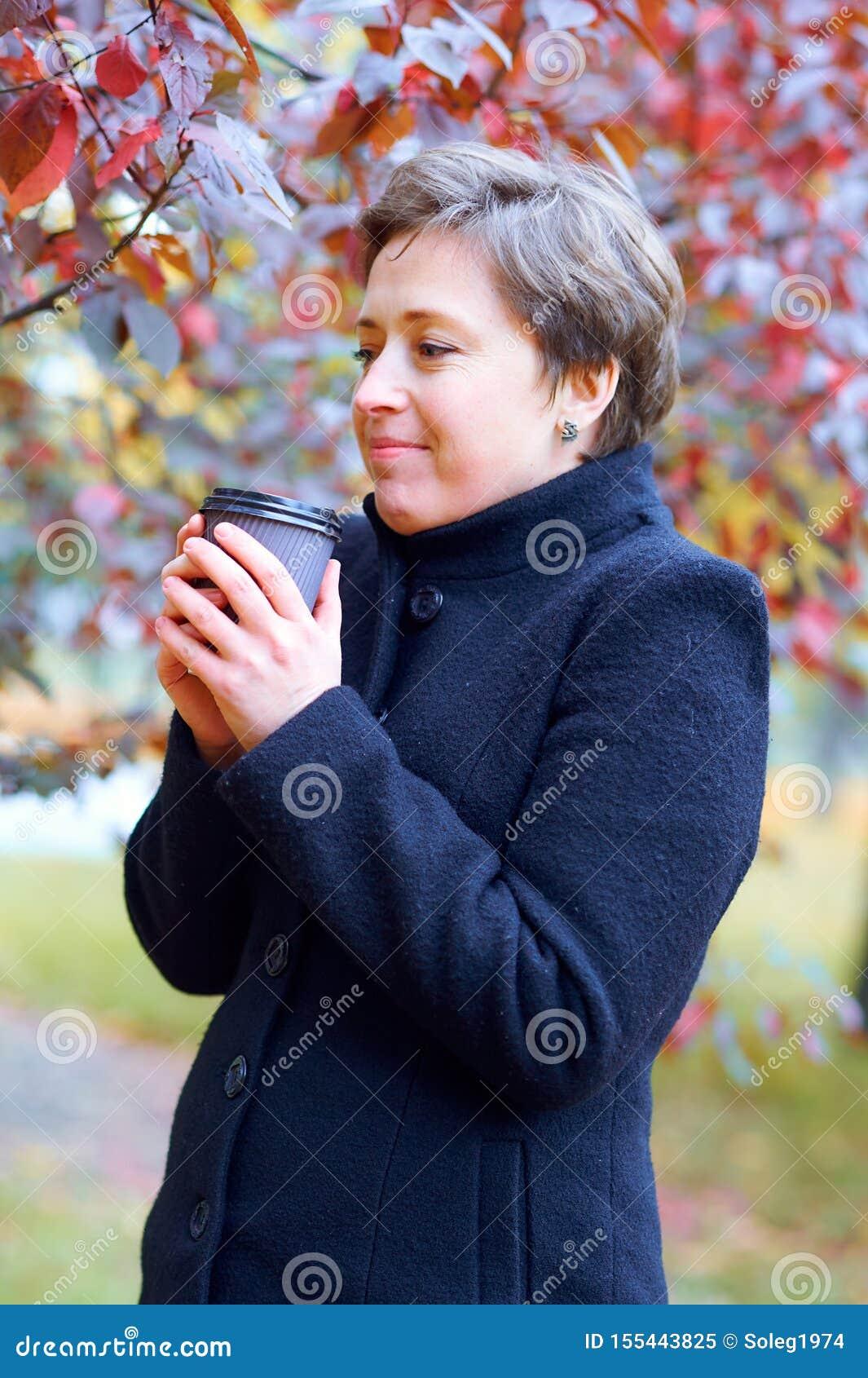 Piękna kobieta pozuje z papierową filiżanką herbata lub kawa w jesieni miasta parku, sezon jesienny