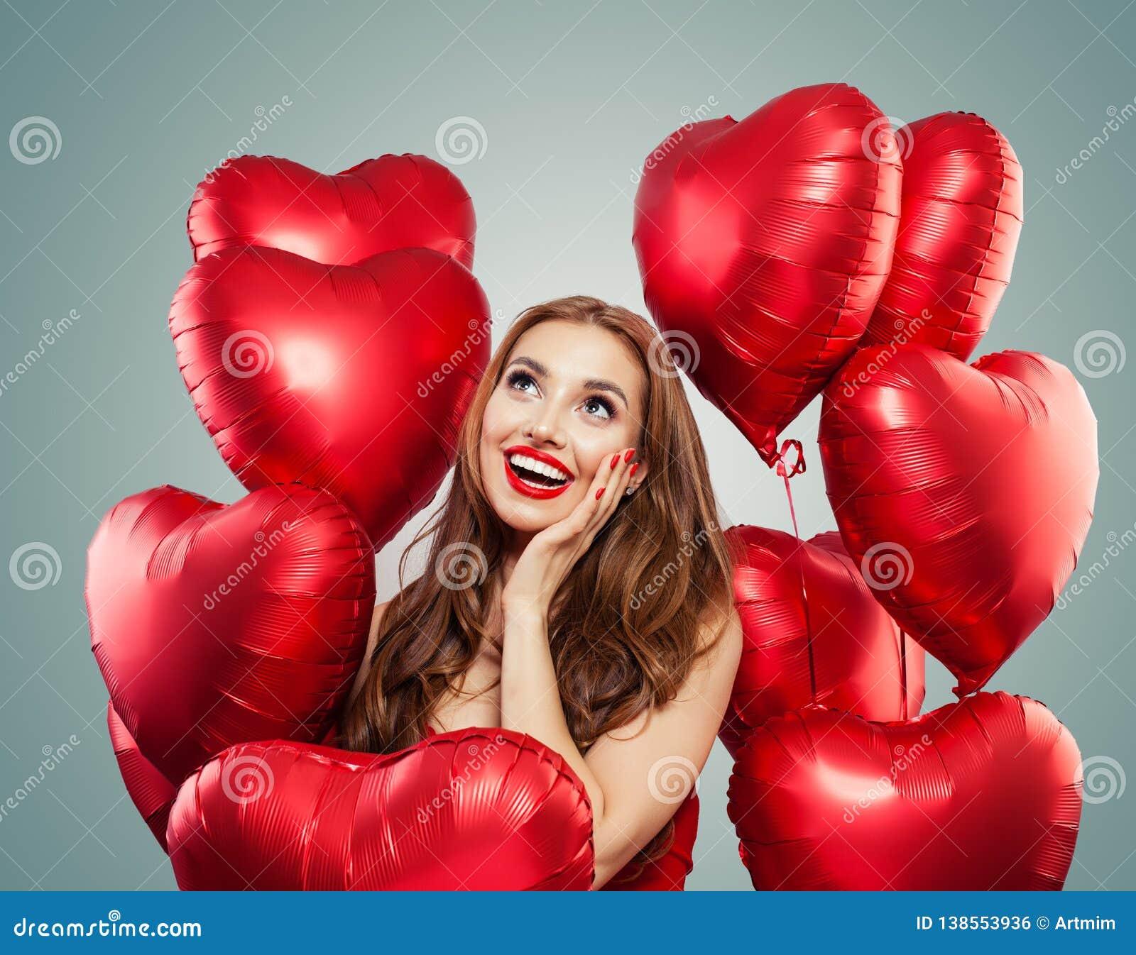 Piękna kobieta trzyma czerwonych kierowych balony Niespodzianka, valentines ludzie i walentynka dzień pojęcie, Ekspresyjni wyrazy