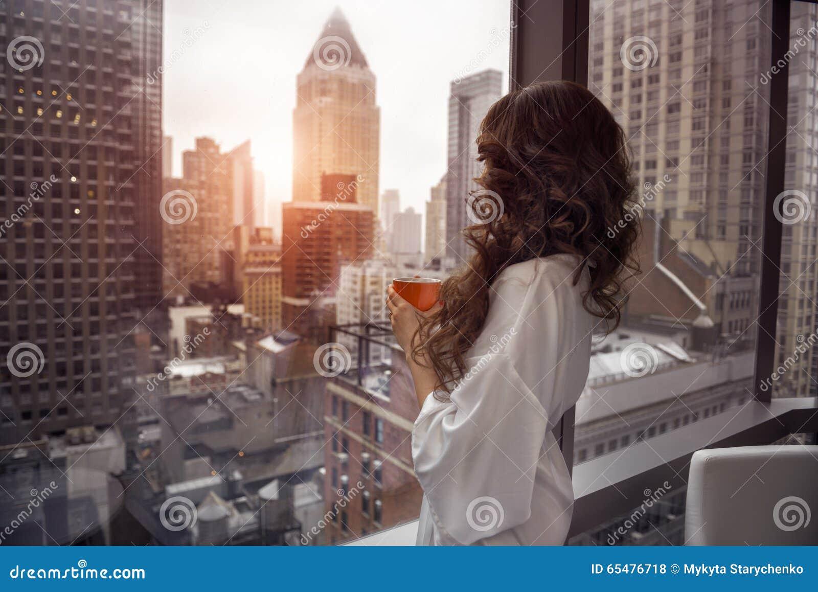 Piękna kobieta trzyma filiżankę i patrzeje okno w luksusowych Manhattan apartament na najwyższym piętrze mieszkaniach