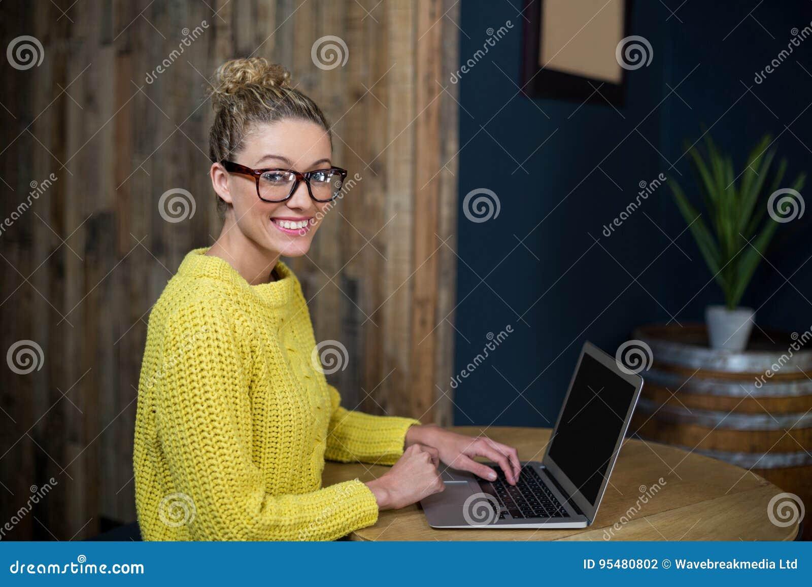 Piękna kobieta używa laptop w café