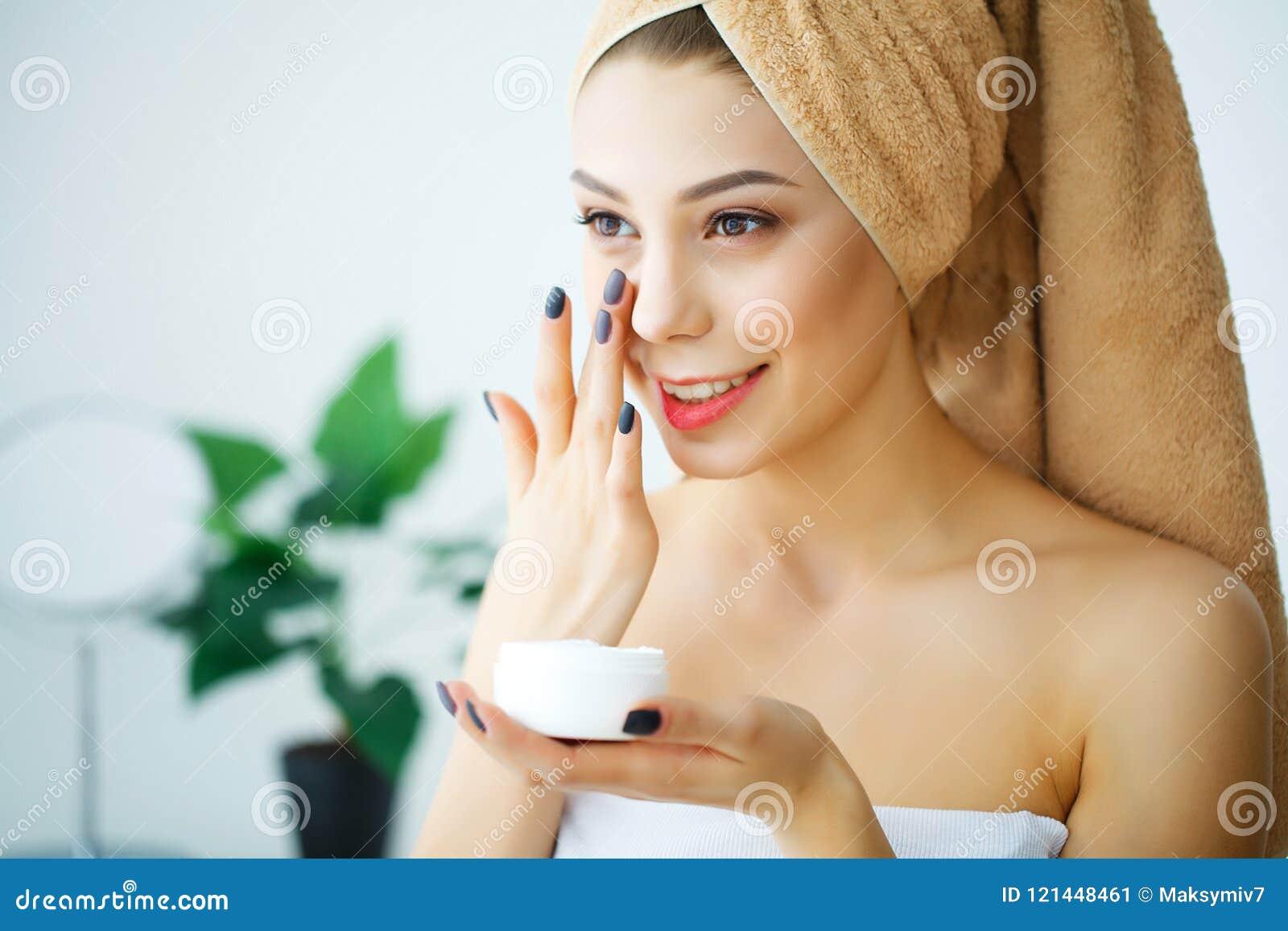 Piękna kobieta używa skóry opieki produkt, moisturizer lub loti,