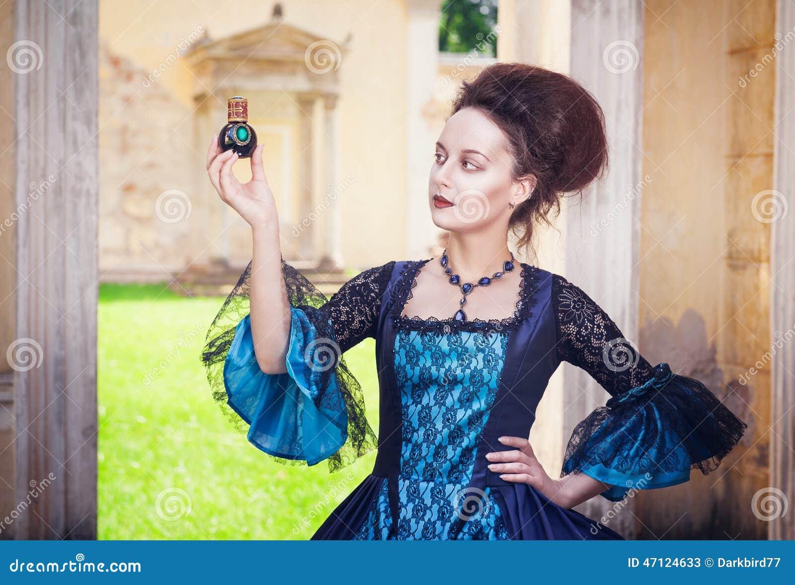 Piękna kobieta w średniowiecznej sukni z pachnidło butelką