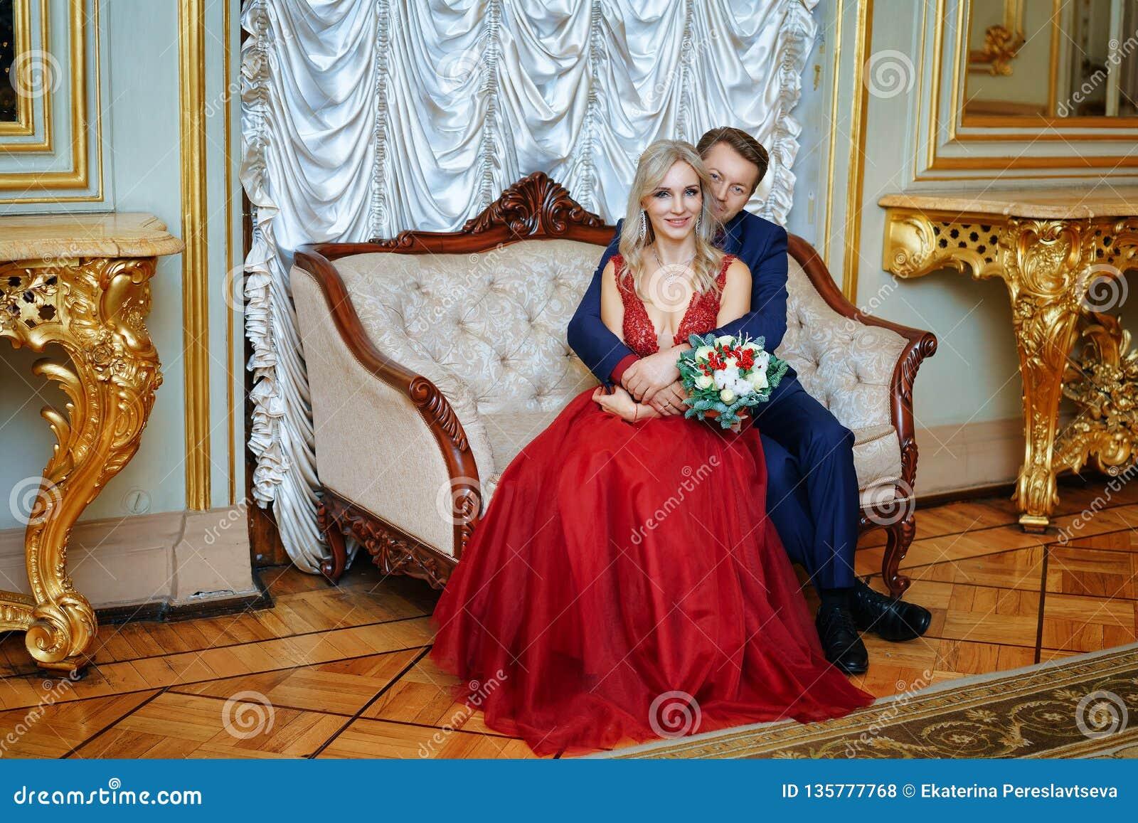 Piękna kobieta w czerwonej sukni z mężczyzny obsiadaniem w krześle państwo młodzi, szczęśliwi nowożeńcy